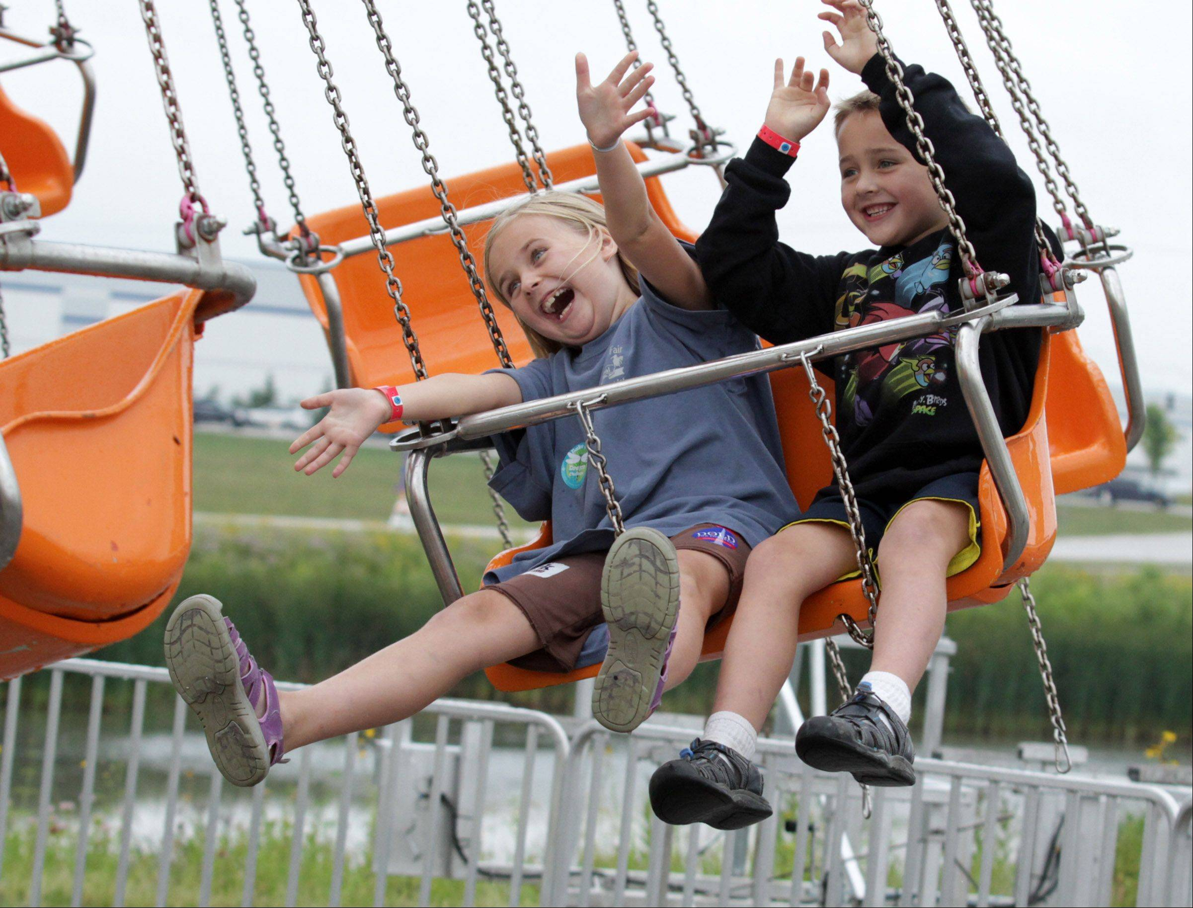 Kailyn, 6, and her brother Dylan May, 9, of Zion ride the spinning swing.