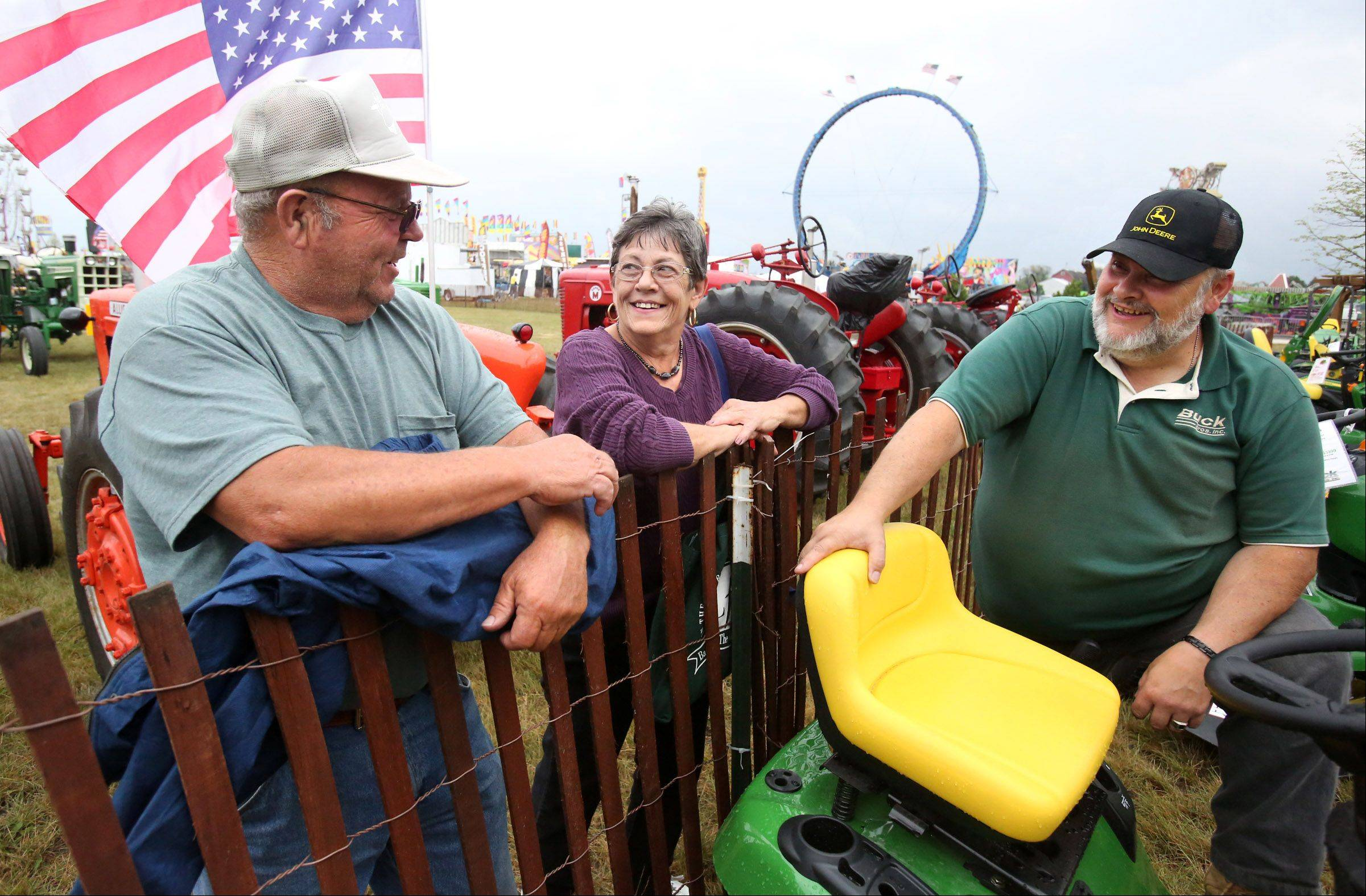 Tom and Jean McCue of Round Lake have a laugh with Gene Felice, right, with Buck Brothers, about Illinois weather after learning that the tractor parade at the Lake County Fair in Grayslake was cancelled due to weather on Friday.
