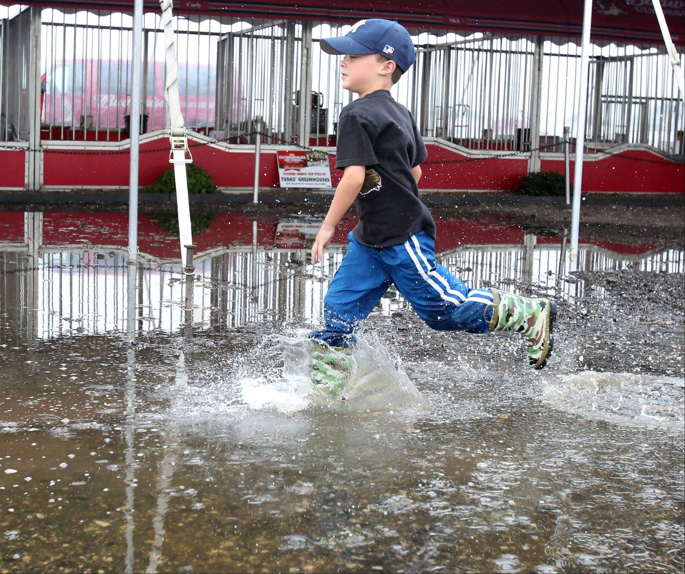 Aidan Bechard, 6, of Grayslake runs through a rain puddle.