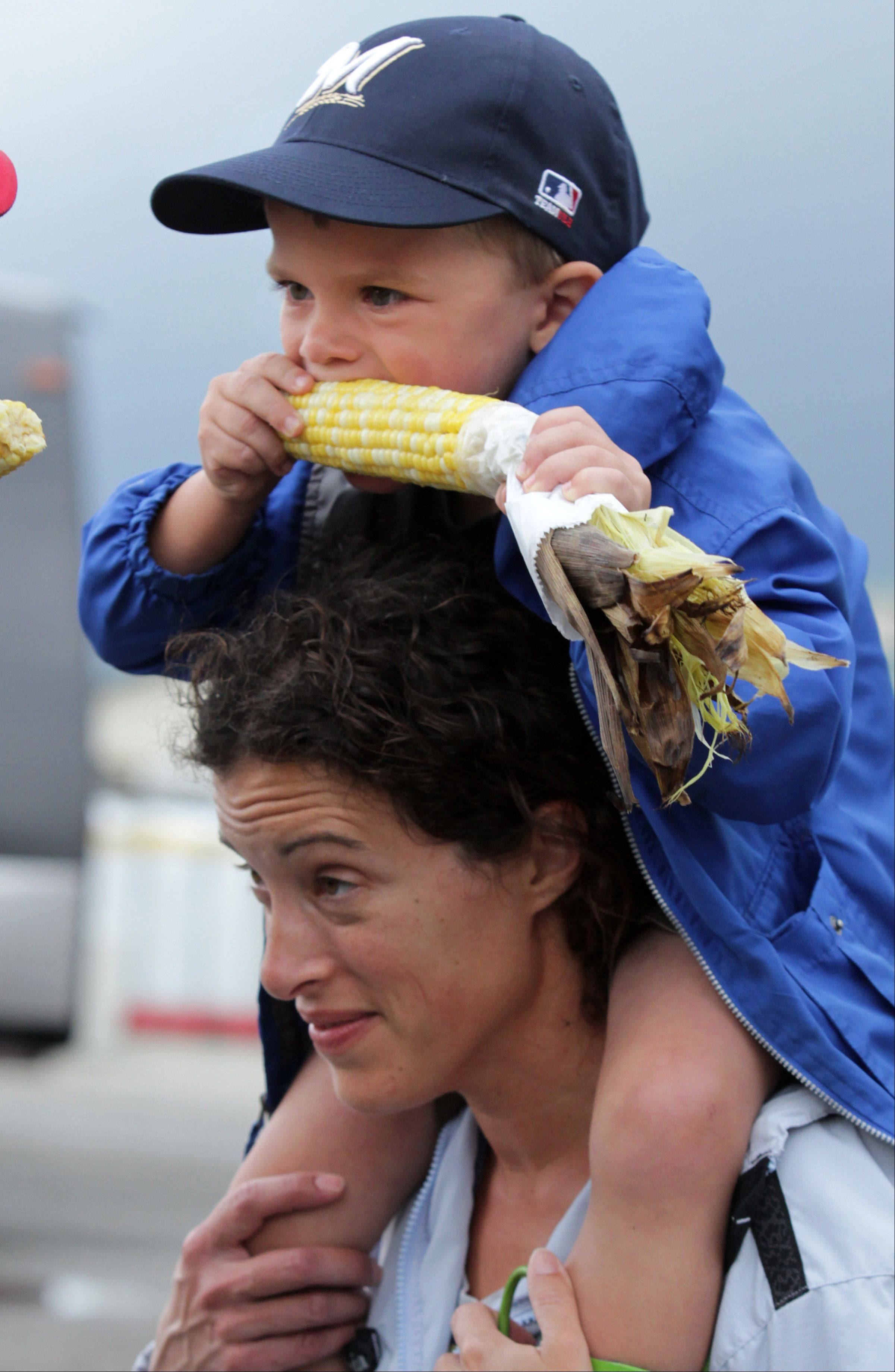 Daniel Bechard, 4, enjoys corn while sitting on his mom, Amy's , shoulders at the Lake County Fair.