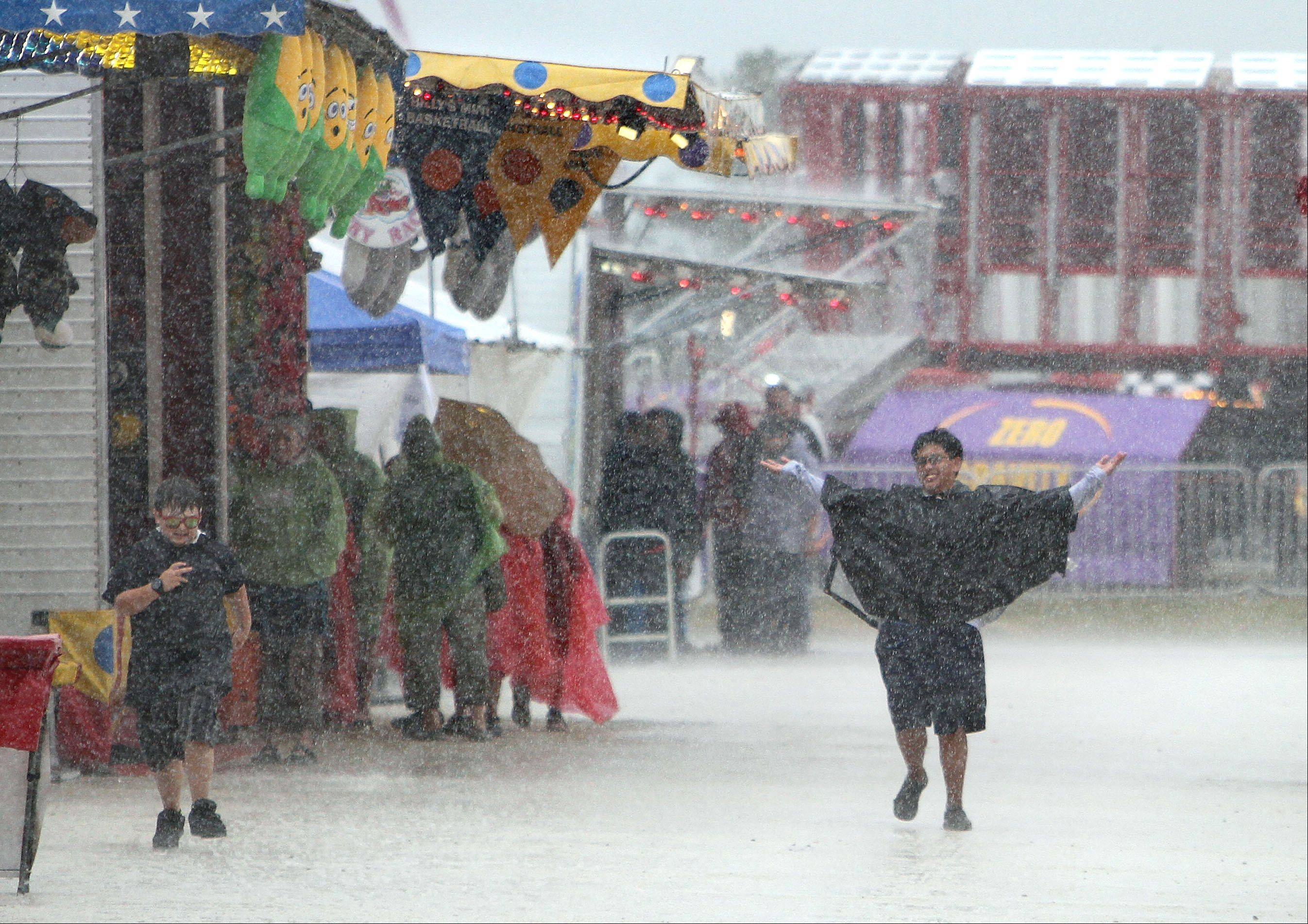 Fair goers make the best of a down pour by playing in the rain.