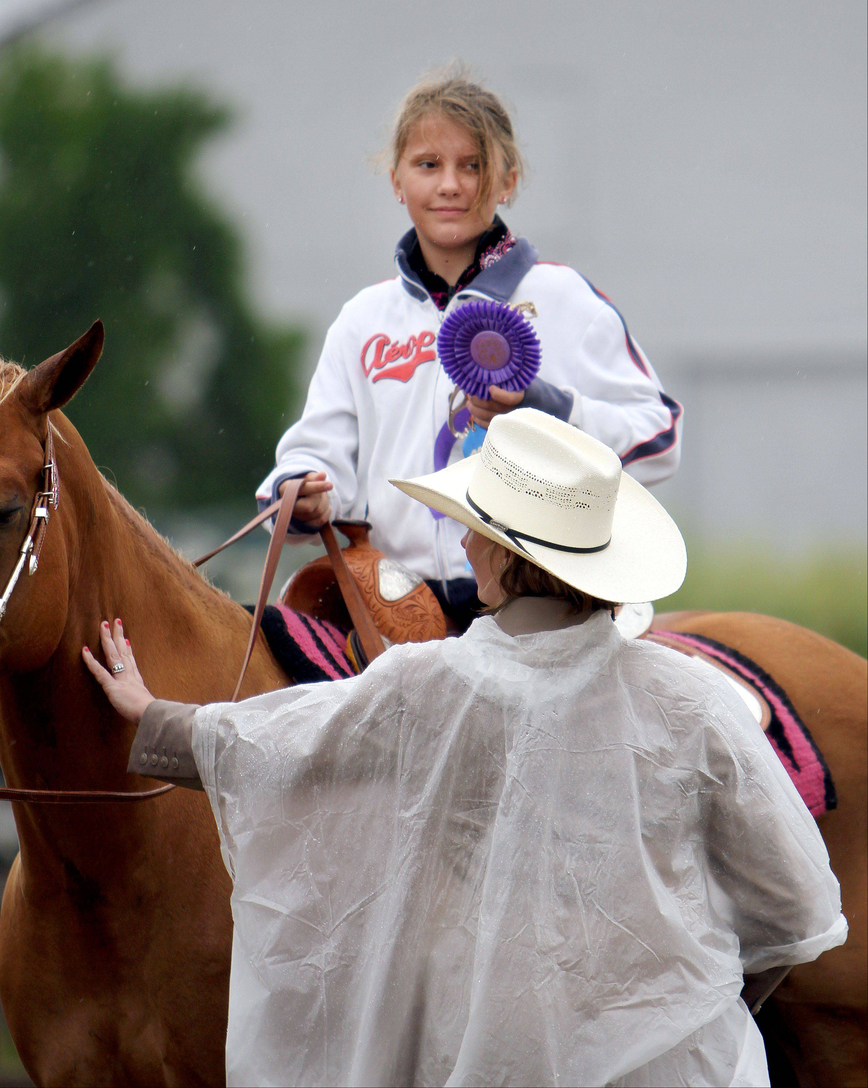 Judge Kim Stanton gives 11-year-old Sandra Zaluski of Spring Grove the grand champion ribbon during beginners western command class judging.