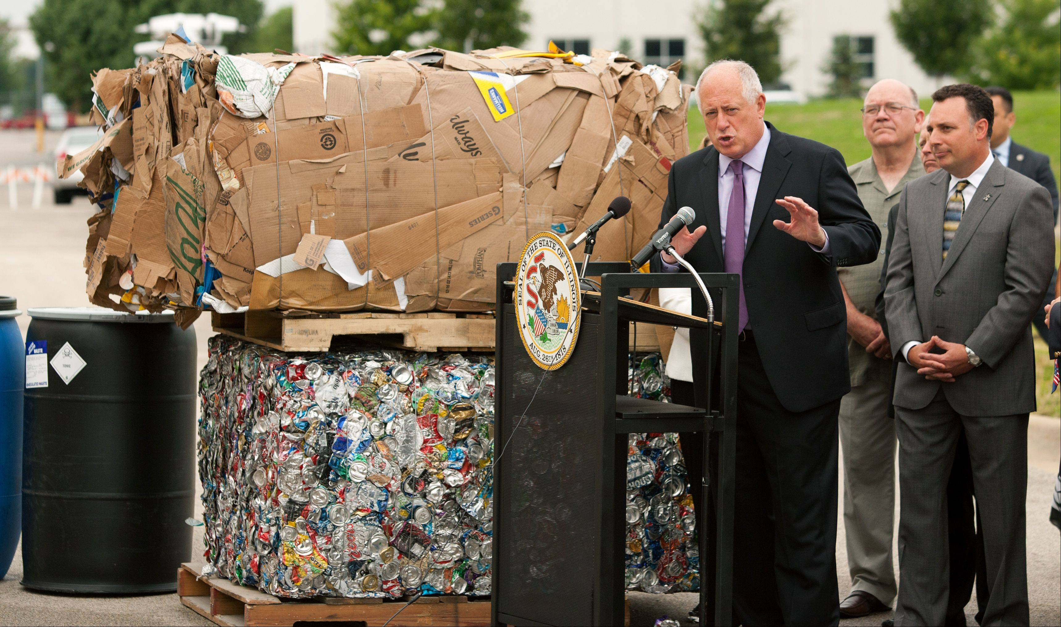 Blocks and barrels of recyclable material serve as the backdrop Friday as Gov. Pat Quinn announces a $900,000 state investment to help the city of Naperville build a new environmental collection center.