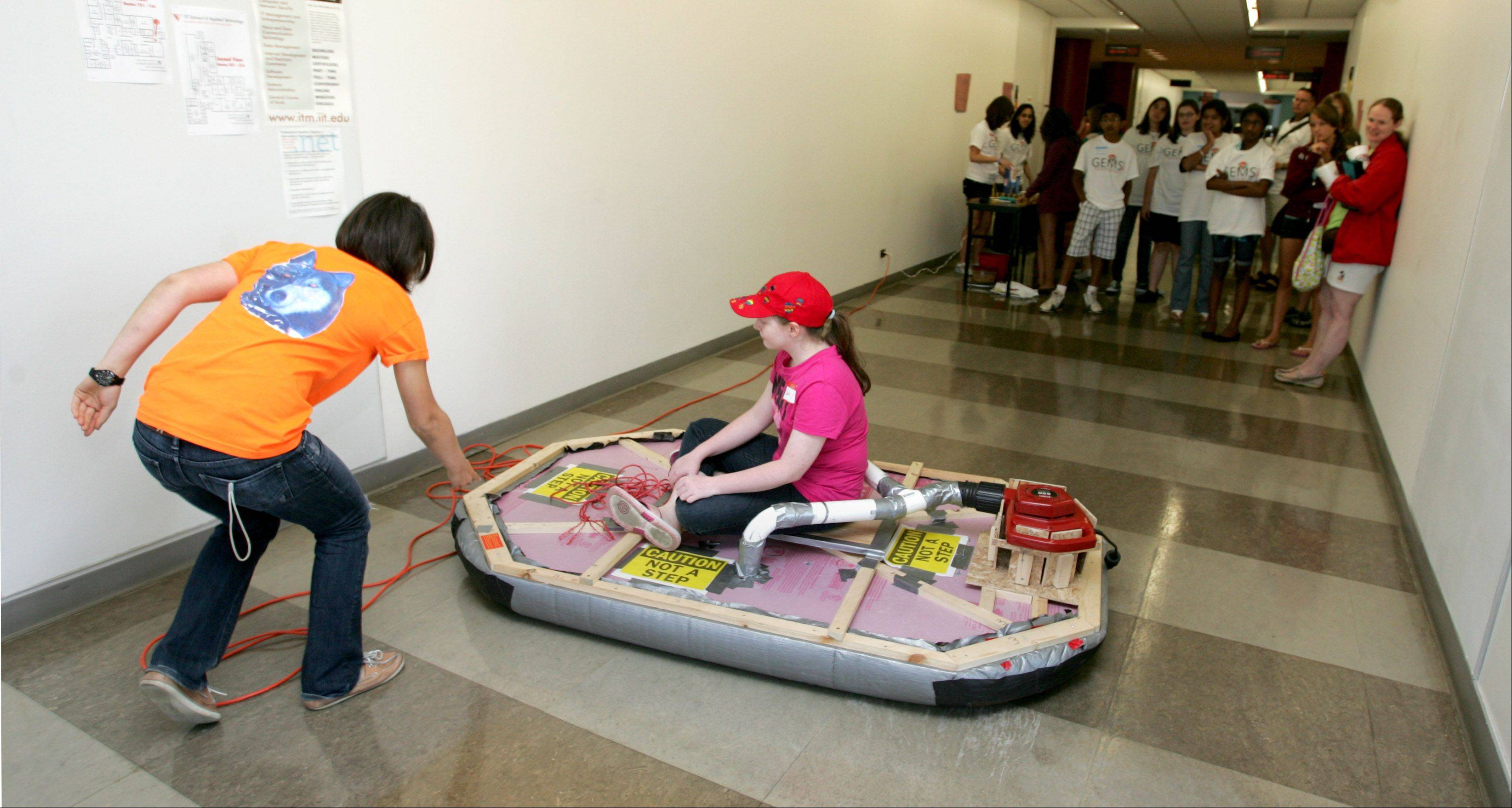 GEMS summer workshop participants watch as Katie Burke of Lisle gets a hovercraft ride from Cari Cesarotti of Naperville North High School during the second annual event for Girl Engineers, Mathematicians and Scientists in 2011. The fourth annual GEMS summer workshop is scheduled for 12:30 to 4:30 p.m. Wednesday, Aug. 7, at Naperville Central High School.