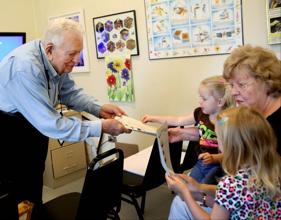 DuBose hands out coloring books to Liana Brunsting, 2, left and sister Amelia, 5, granddaughters of Joyce Brunsting of Naperville during their visit to Wanda's Honey House.