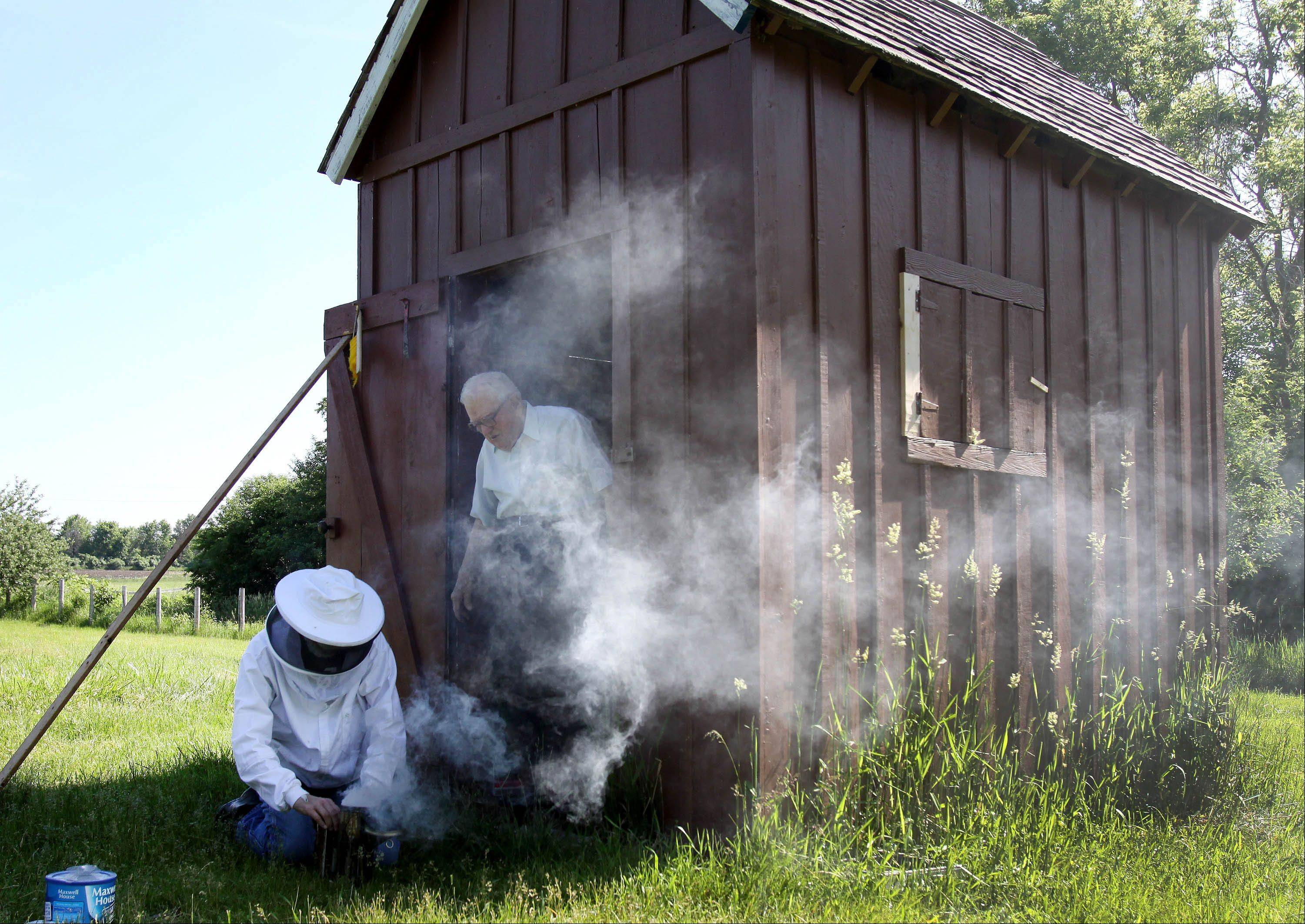 DuBose comes out of the shed as volunteer Duane Marski gets the smoker ready to tend to the bees.