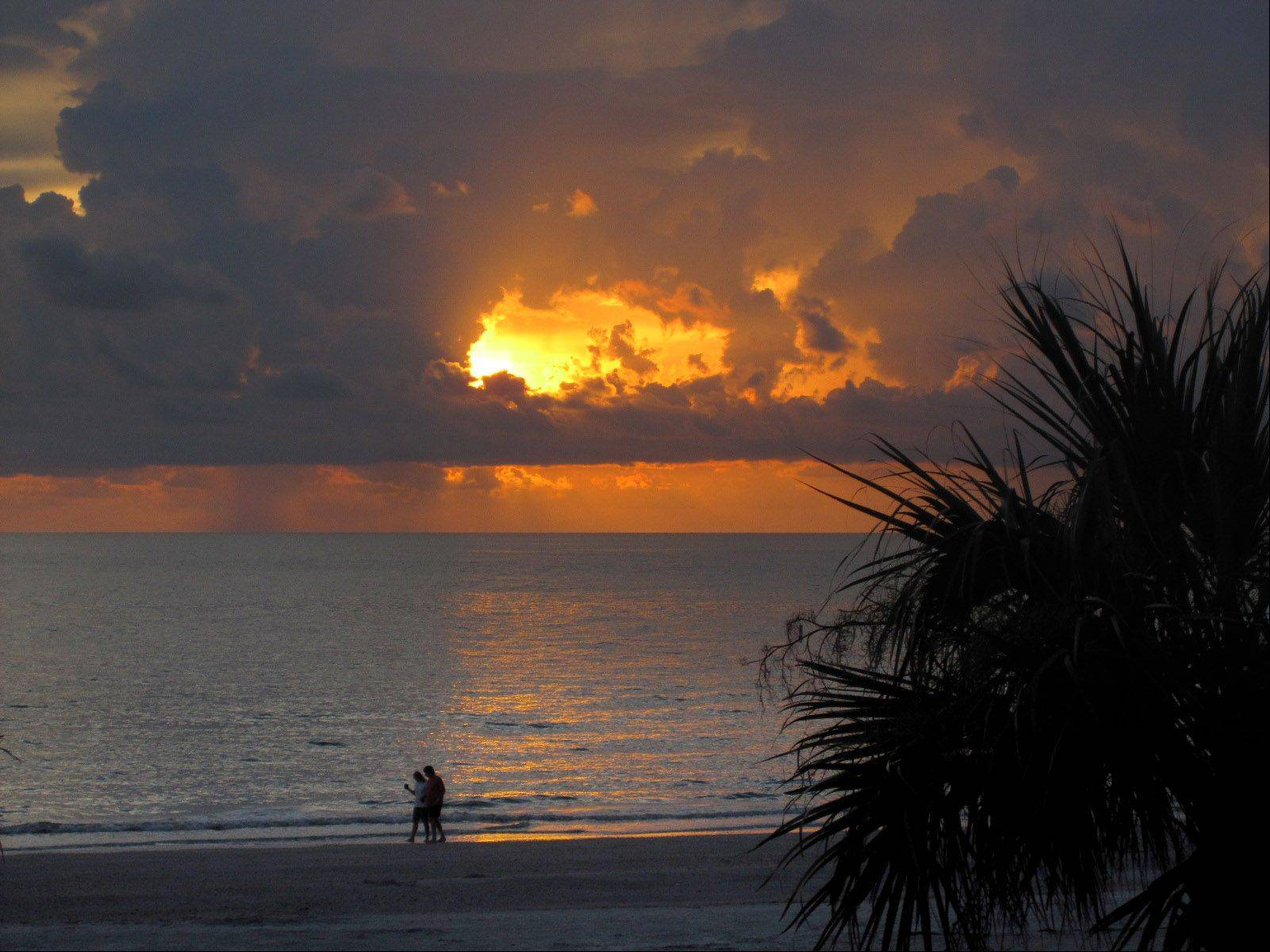 A couple walks on the beach collecting shells in Indian Rocks Beach, FL following a storm the evening of July 11.