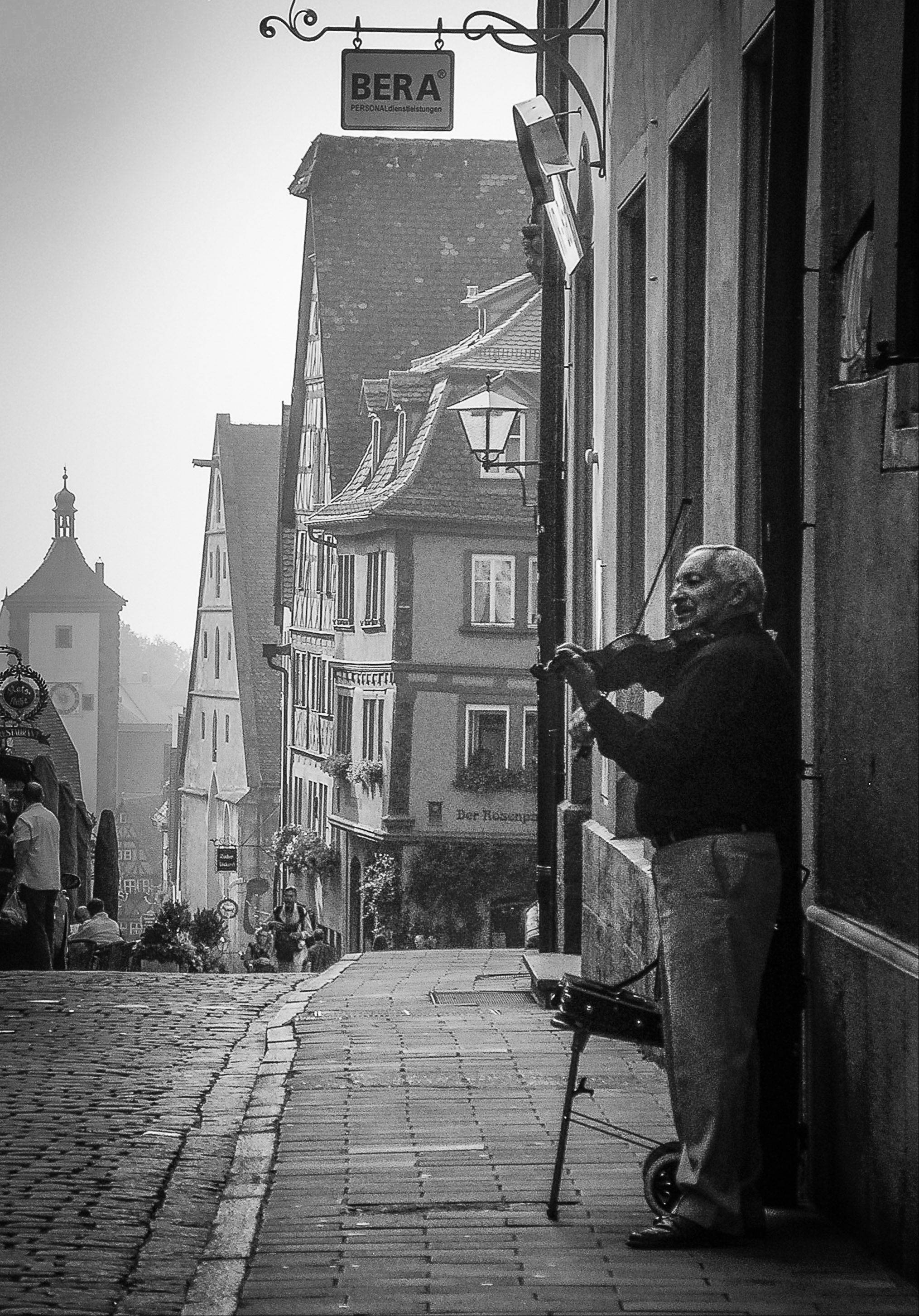 A violinist plays for donations on the cobblestone streets of Rothenburg, Germany early in the morning in September 2009. Rothenburg is a walled medieval city that survived World War II and is a must see destination in Germany.