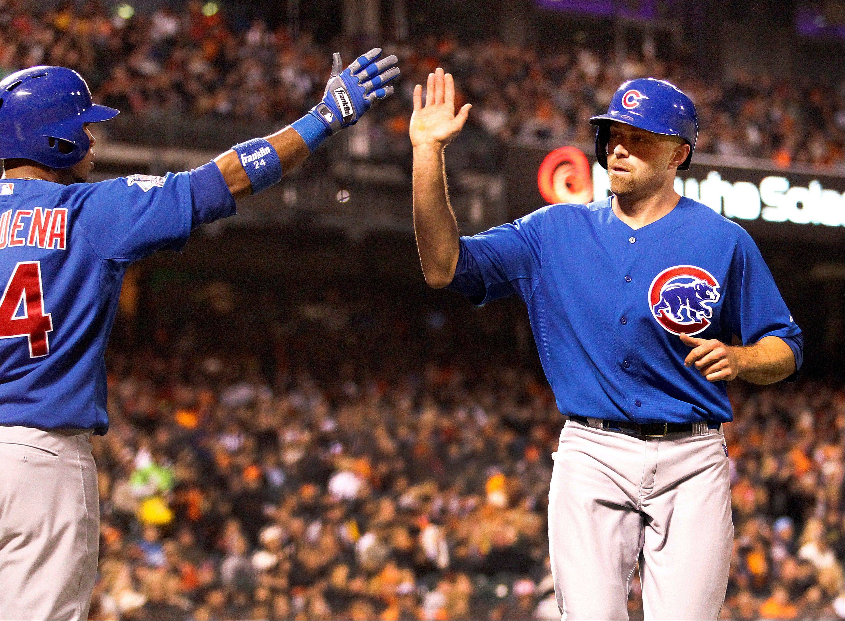 Cubs outfielder Nate Schierholtz, right, is congratulated by teammate Luis Valbuena, left, after scoring a run on a single Starlin Castro against the San Francisco Giants in Friday's sixth inning.