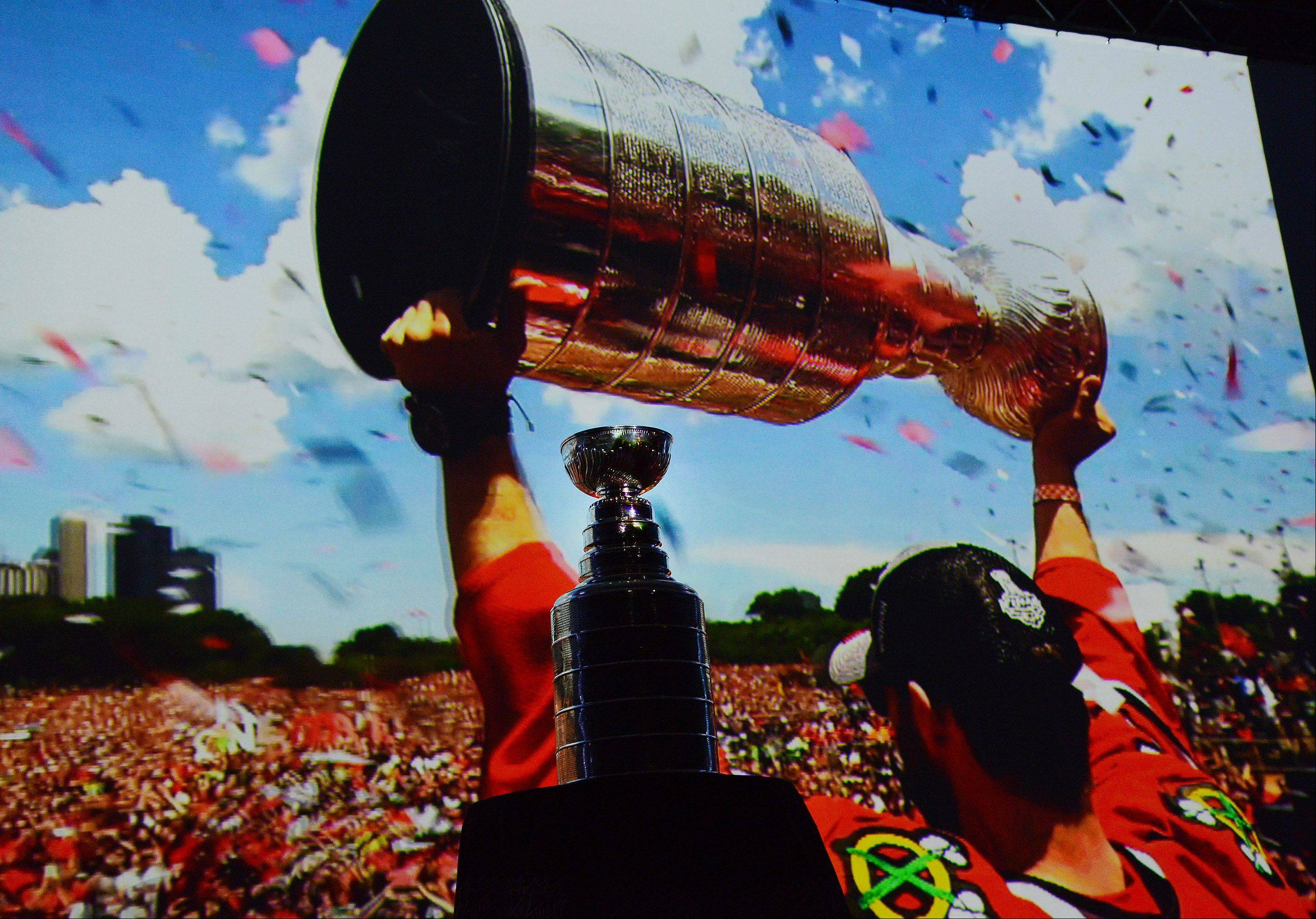 The Stanley Cup stands in front of a video of the Grant Park rally.
