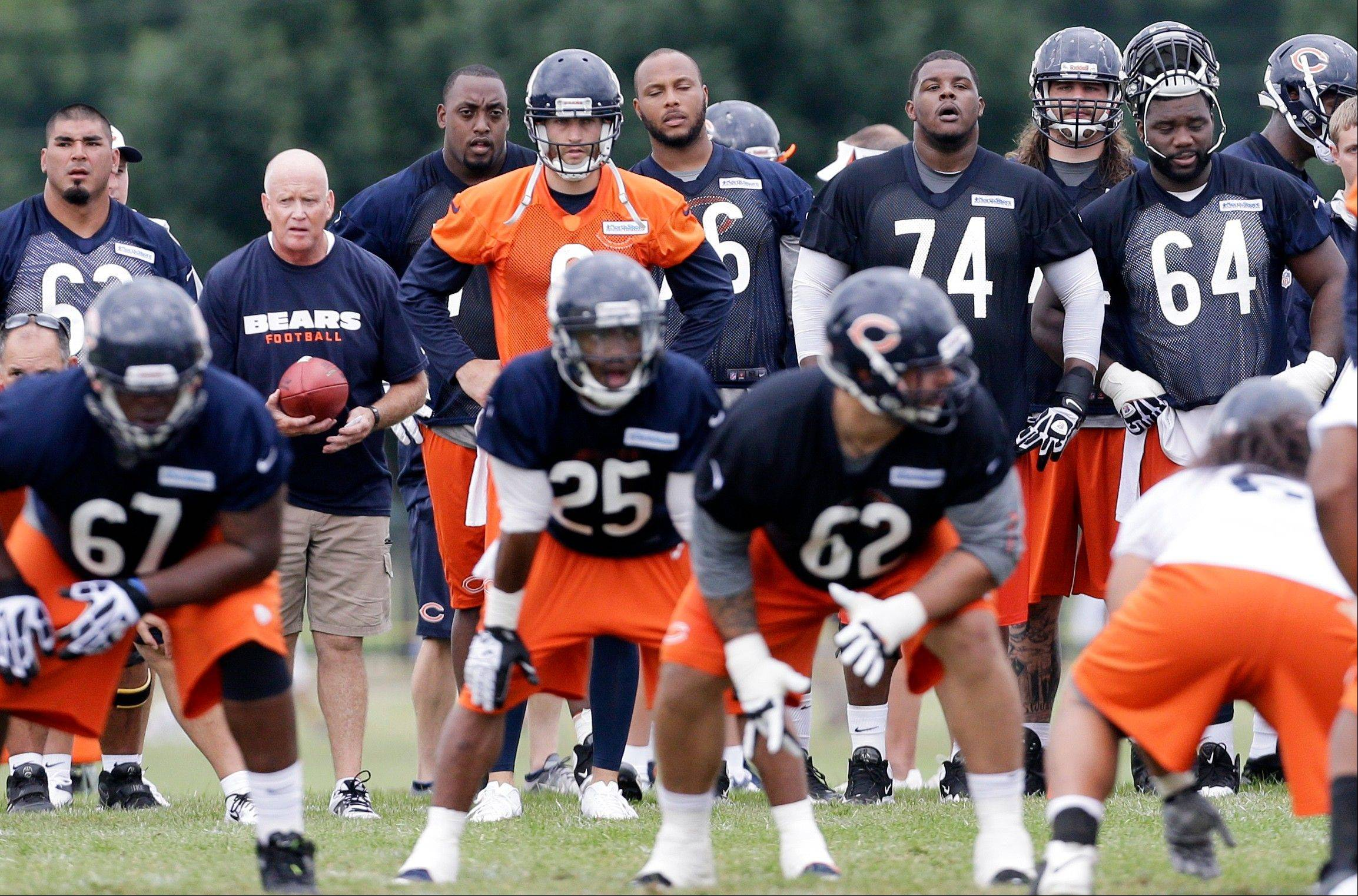 Chicago Bears quarterback Jay Cutler , center rear, watches teammates.