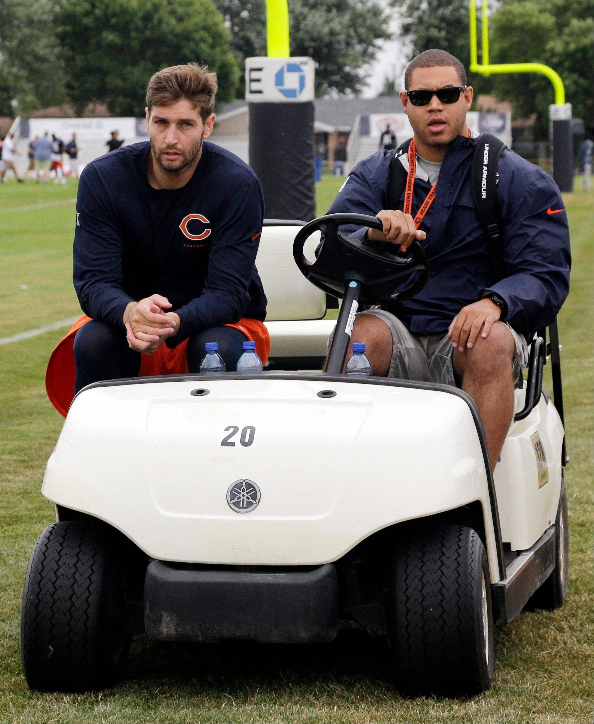 Chicago Bears quarterback Jay Cutler, left, leaves with media relations assistant Jared Ellerson.