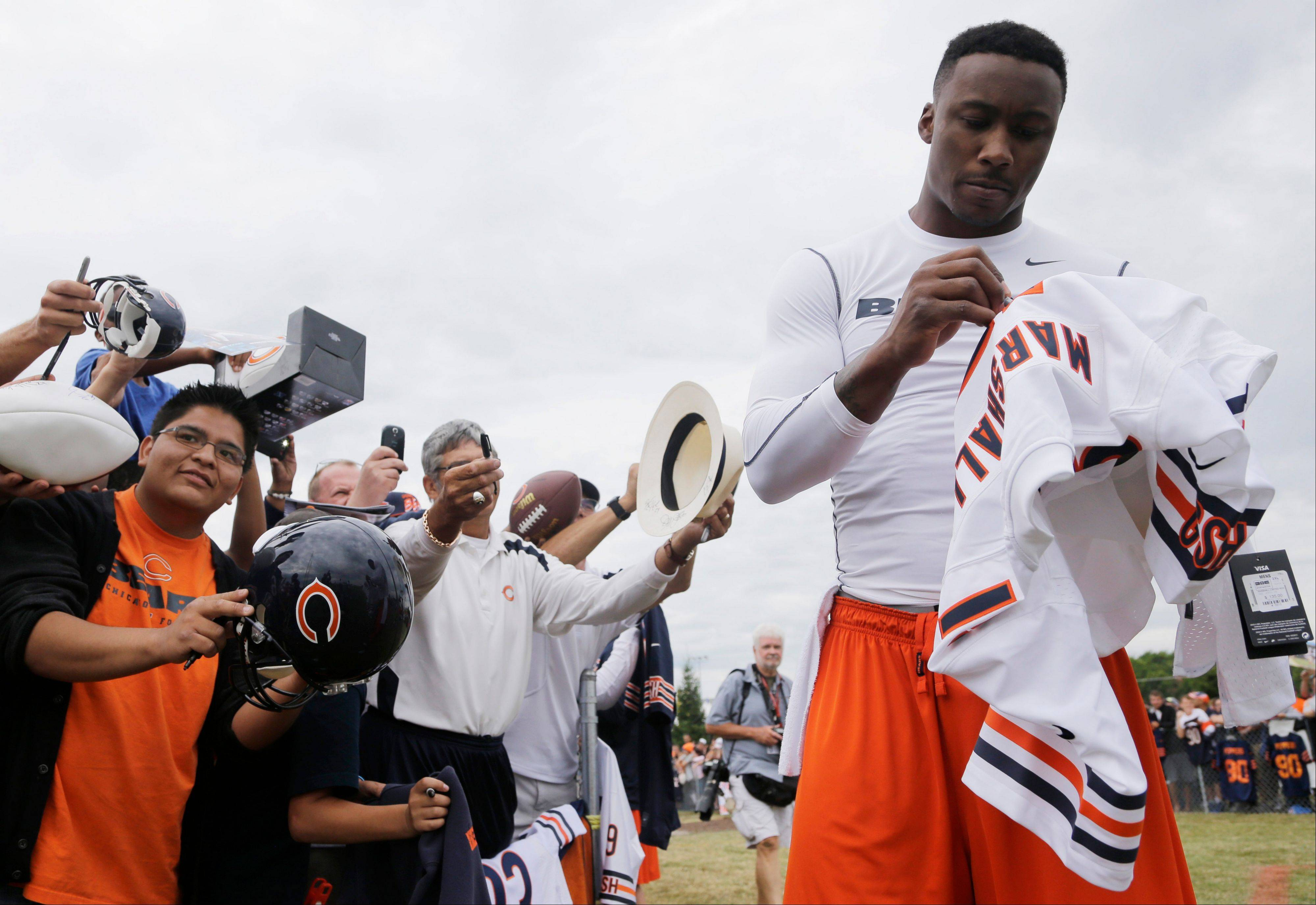 Chicago Bears wide receiver Brandon Marshall, right, signs autographs for fans.
