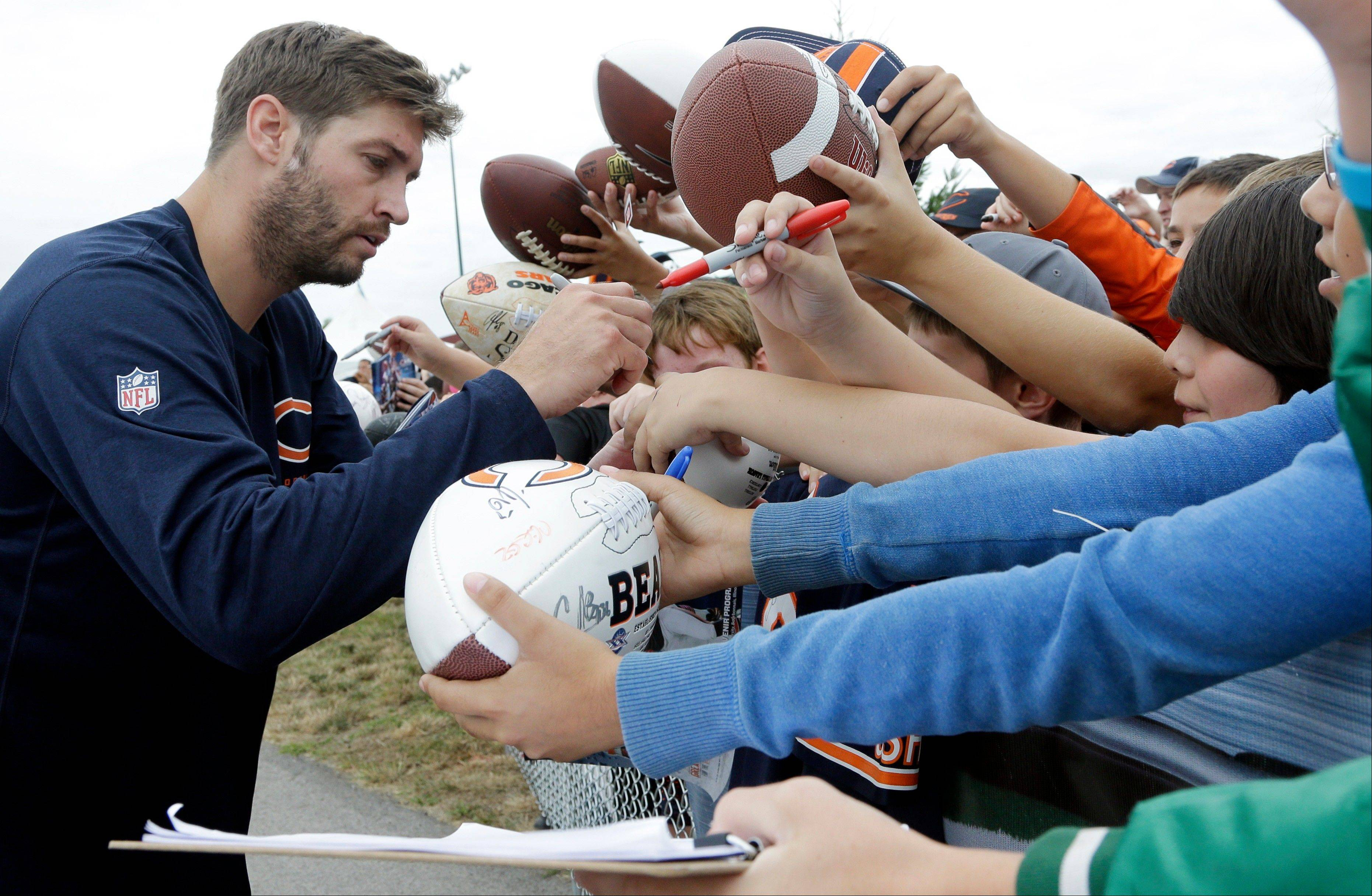 Chicago Bears quarterback Jay Cutler, left, signs autographs for fans.