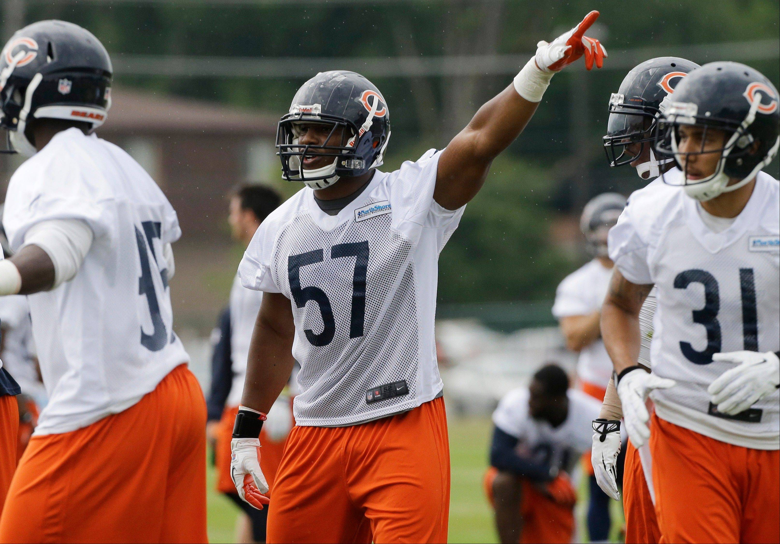 Chicago Bears linebacker Jonathan Bostic points as he talks to teammates.