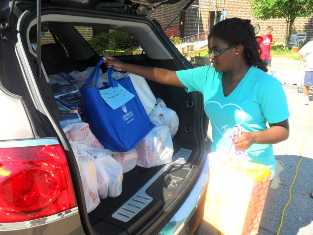 Kelly Moody, a previous HSP intern, helps place groceries into a delivery driver's car for the Senior Citizen Project.