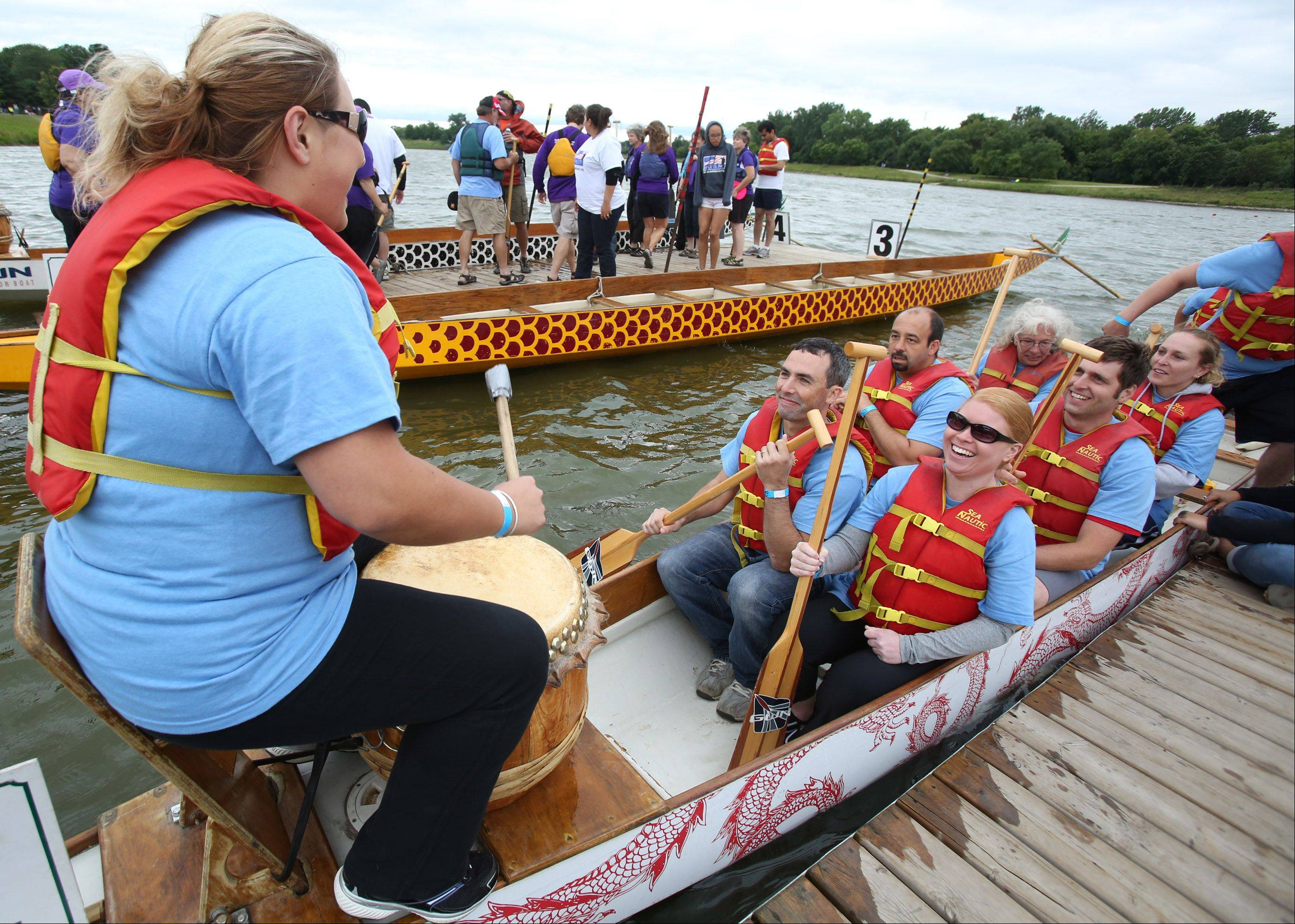 Karolina Baran drums to get her Walgreens Chicago Suburbs team motivated at the Walgreens Chicago International Dragon Boat Festival Saturday at Lake Arlington in Arlington Heights.