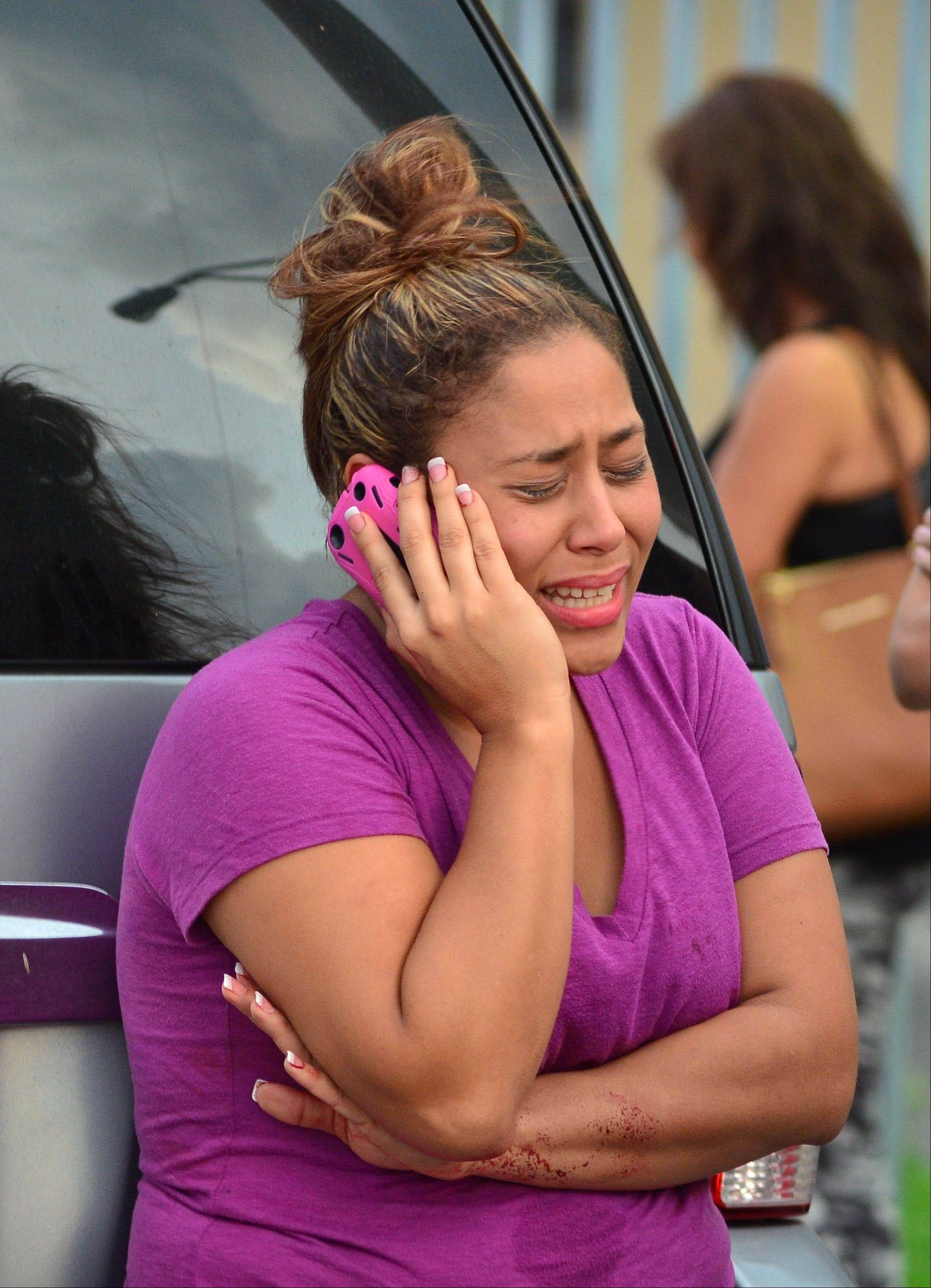 A woman talks on the phone outside an apartment building at the scene of a fatal shooting in Hialeah, Fla., early Saturday, July 27. A gunman holding hostages inside the apartment complex killed six people before being shot to death by a SWAT team that stormed the building early Saturday following an hours-long standoff, police said.