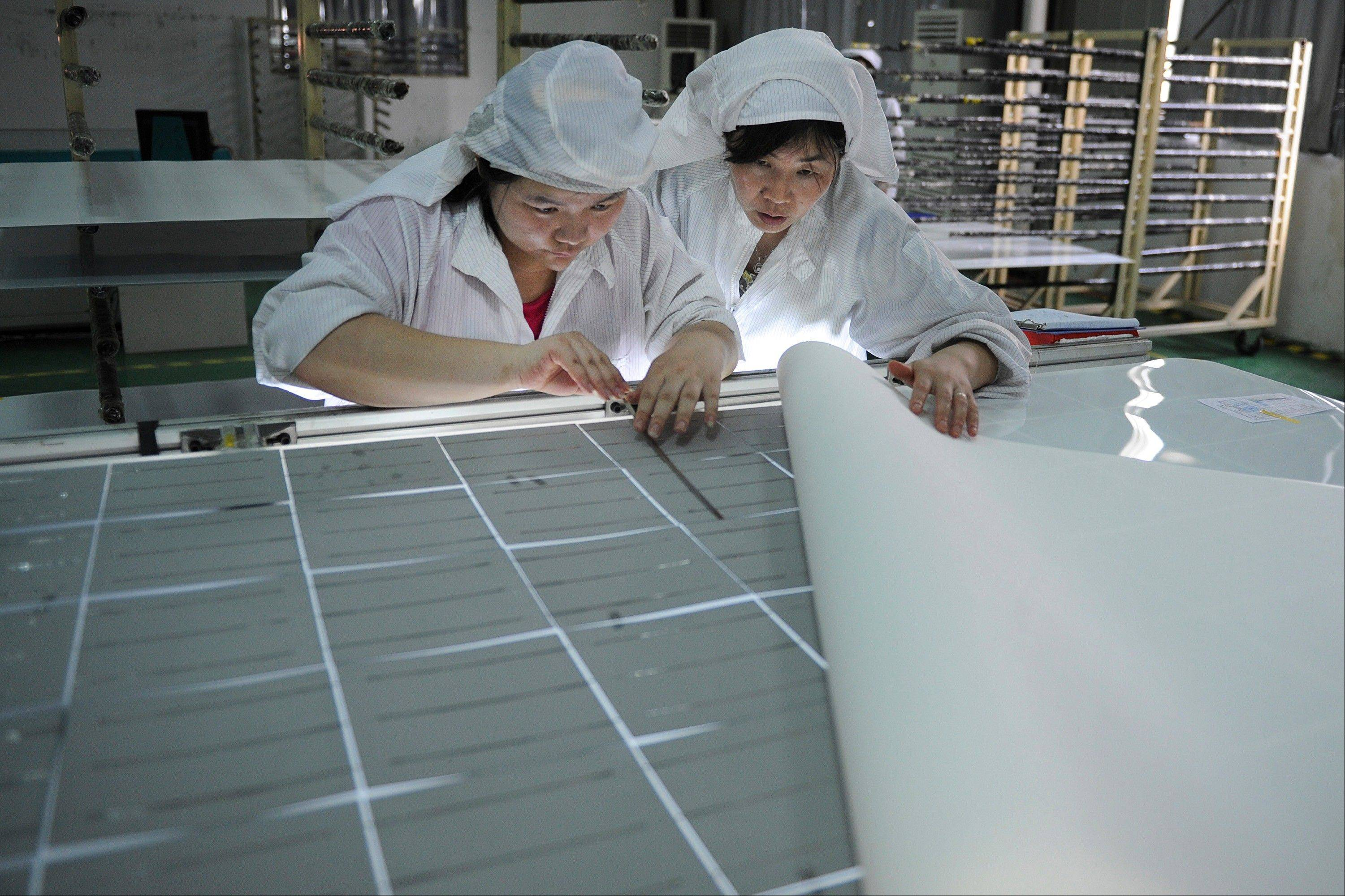 Workers assemble solar panels at a factory in Hefei, in central China's Anhui province.
