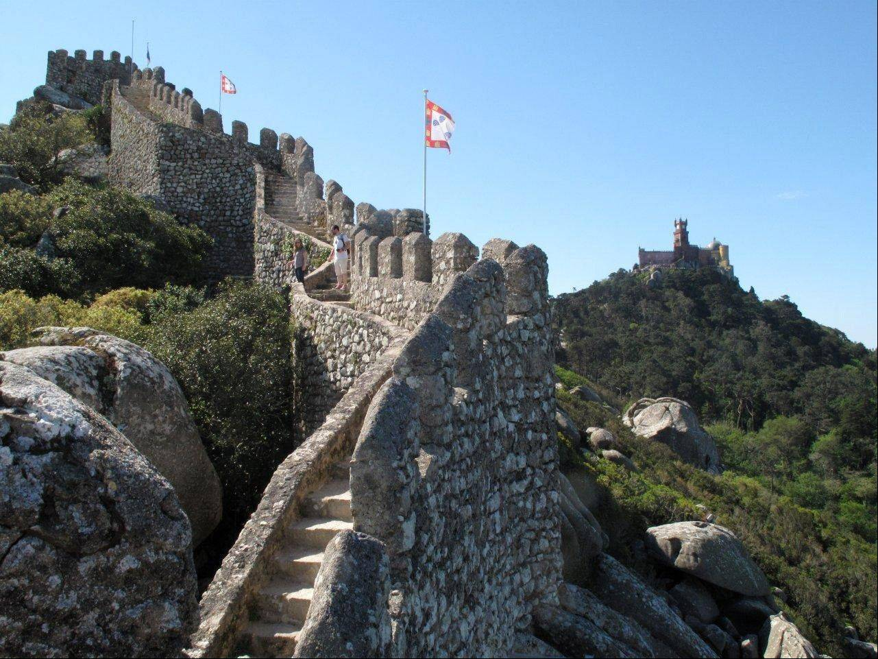Pena Palace in the distance with the steps of the Moorish Castle in the foreground in Sintra, Portugal.