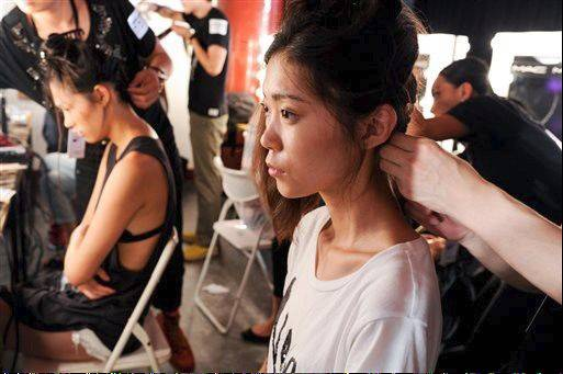 Models are prepared for a fashion show by New York-based designers in Beijing, China.