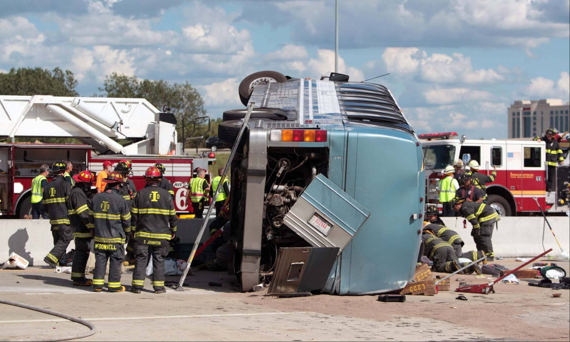 Firefighters work to extricate people from a bus crash Saturday in Indianapolis.