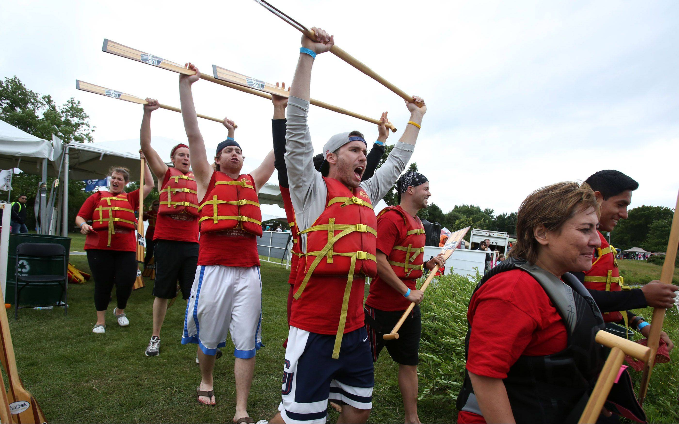 Red Fitness Center paddlers head to their dragon boat at the Walgreens Chicago International Dragon Boat Festival Saturday at Lake Arlington in Arlington Heights.