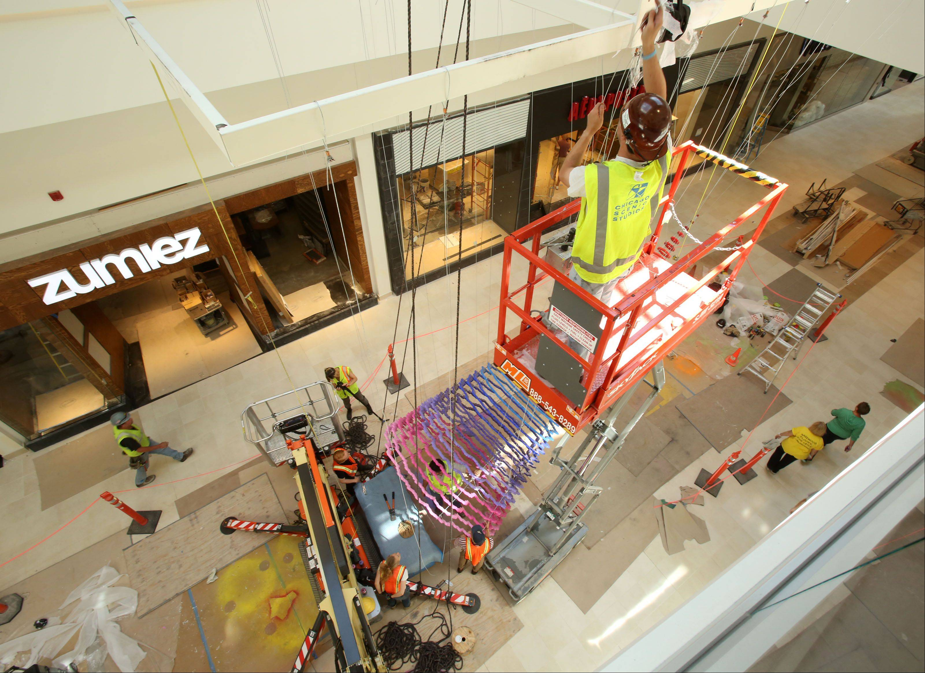Workers prepare to lift an art piece by Jen Stark inside the Fashion Outlets of Chicago in Rosemont on Wednesday, July 24, 2013. Eleven artist are featured throughout the mall.