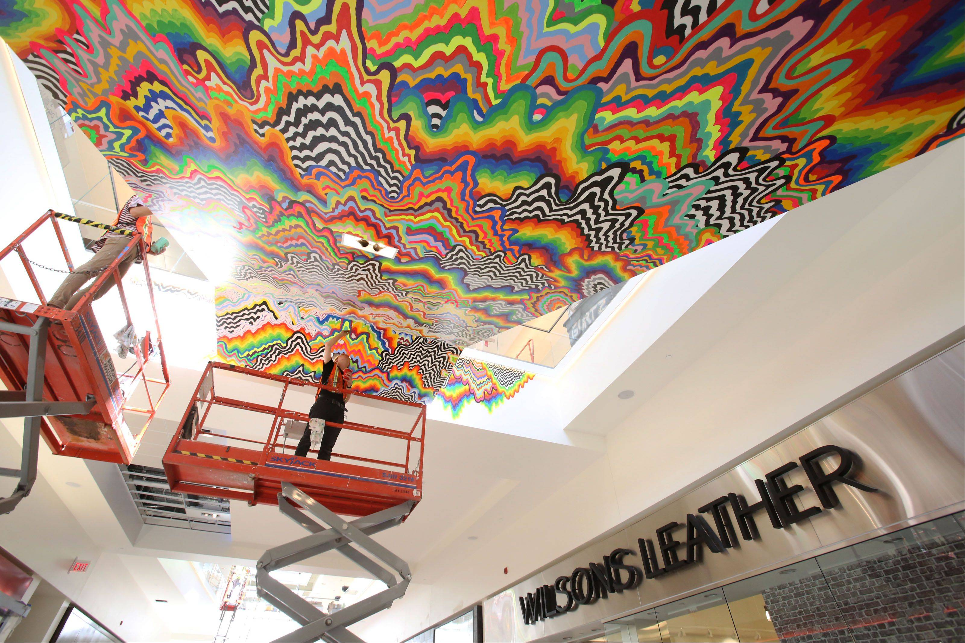 Artist workers paint an art piece by Jen Stark inside the Fashion Outlets of Chicago in Rosemont on Wednesday, July 24, 2013. Eleven artist are featured throughout the mall.