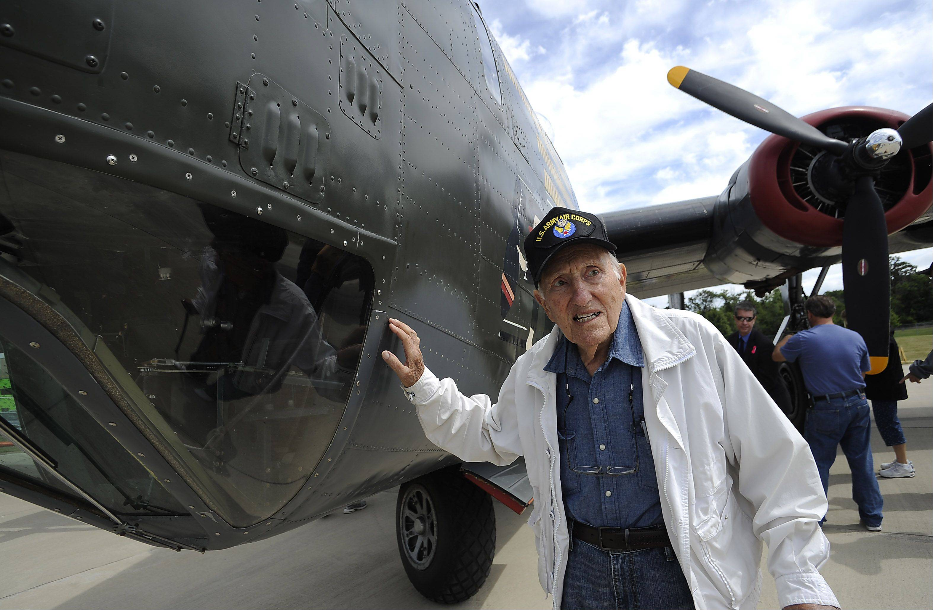 Jim Brahos, 90, of Beach Park, Illinois touches the fuselage of the B-24 Liberator, just like the one he was a tailgunner in during World War II serving the years 1942 through 1945 at Chicago Executive Airport on Saturday.