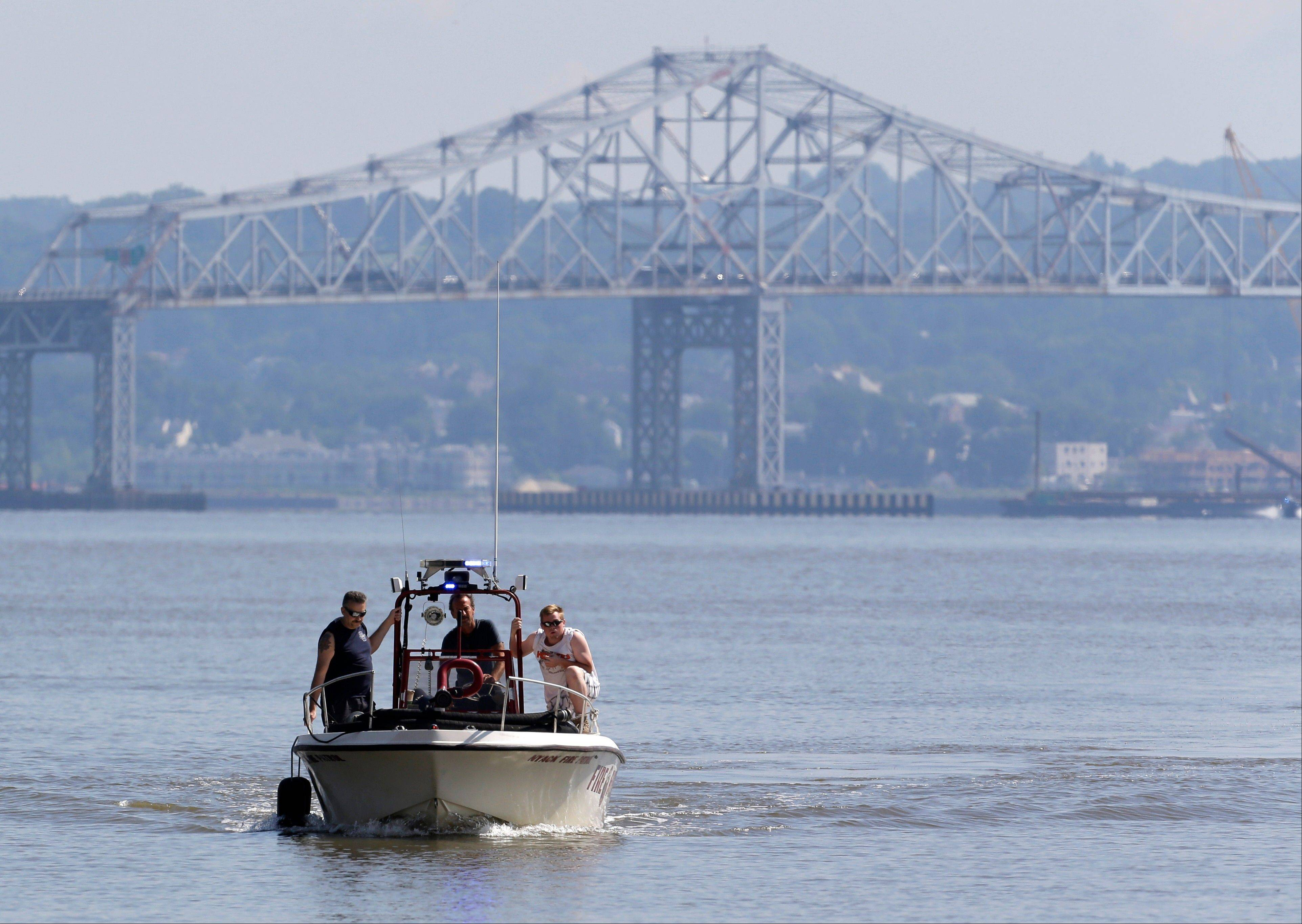 Rescue workers on a boat search the Hudson River south of the Tappan Zee Bridge for two people who are believed to have fallen into the water during a boat crash in Piermont, N.Y. on Saturday, July 27. Two people are missing and four others are injured after their boat struck a barge under the bridge, according to the Coast Guard.