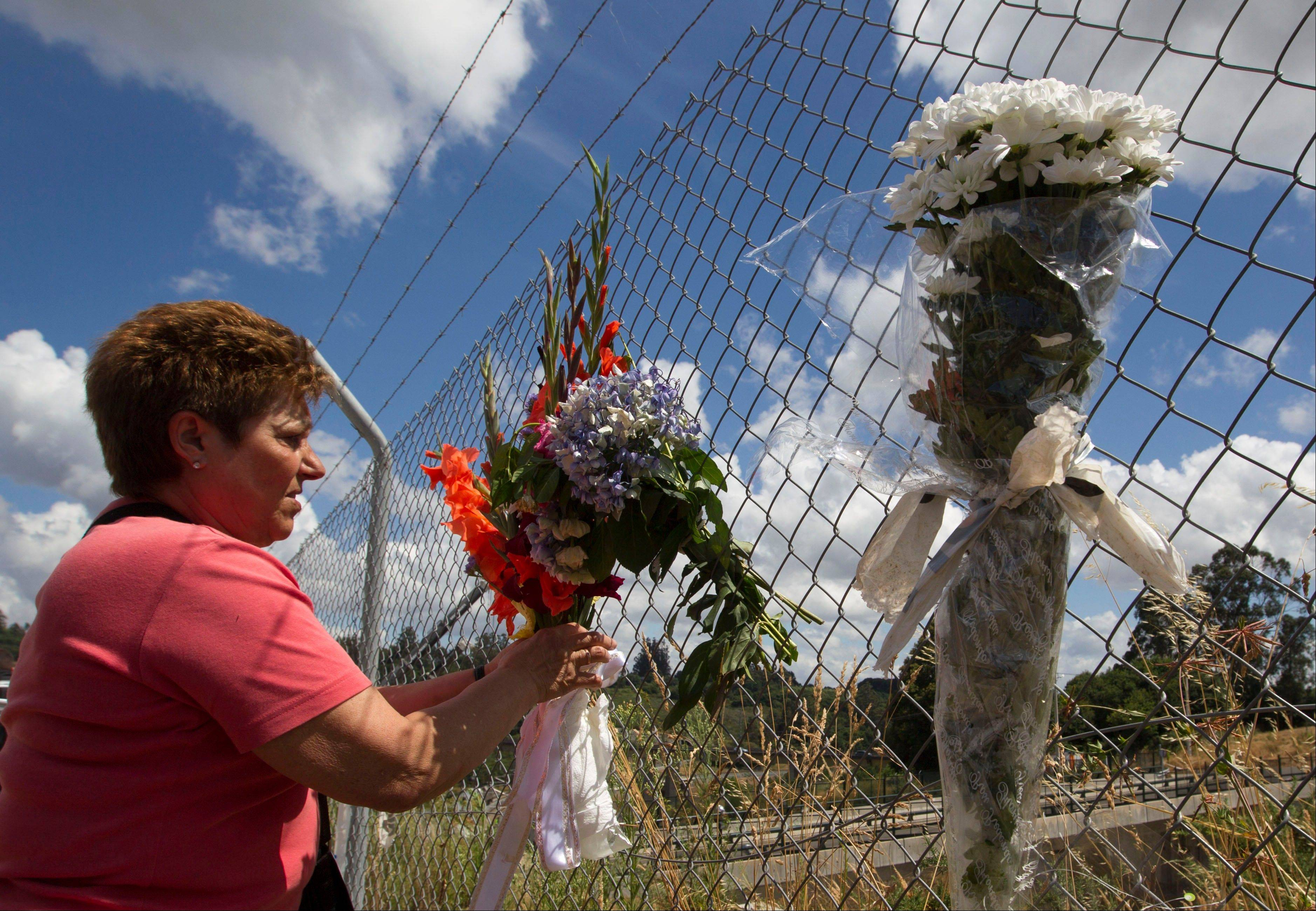 A woman fixes a flower branch on a fence above the railway tracks at the spot of the train crash in Santiago de Compostela, Spain, Saturday July 27. Spain's interior minister Jorge Fernandez Diaz says the driver whose speeding train crashed, killing 78 people, is now being held on suspicion of negligent homicide.