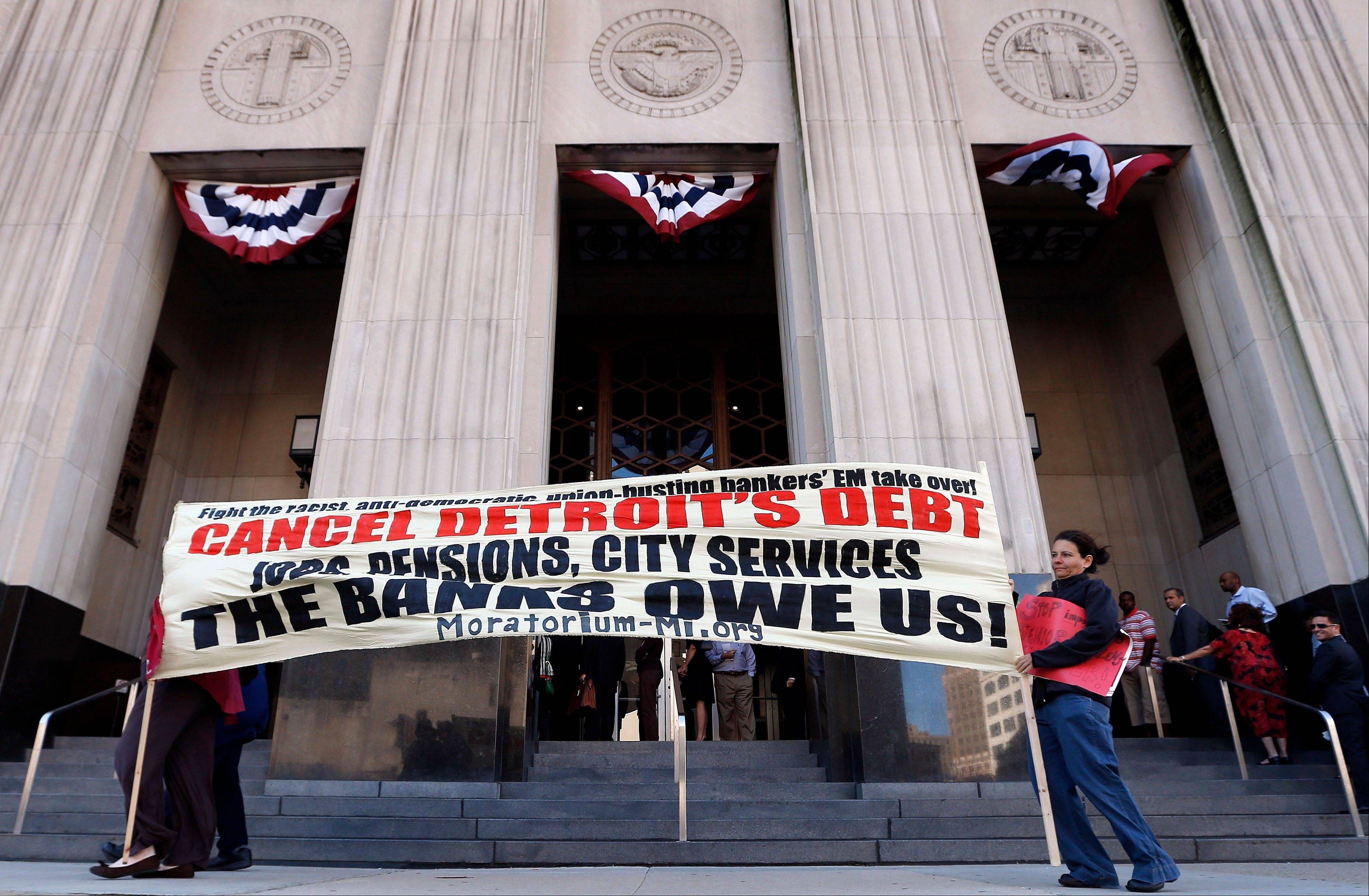 On July 24, protesters carry a sign outside the Levin Federal Courthouse in Detroit. Detroit's historic bankruptcy filing is a major setback for public sector unions that have spent years trying to ward off cuts to the pensions and benefits of government workers. If the city succeeds, it could put into jeopardy a key bargaining tool for unions that have often deferred higher wages in favor of more generous pension benefits. And it could embolden other financially troubled cities dealing with pension shortfalls to consider bankruptcy, or at least take a harder line with their unions in negotiating cuts.