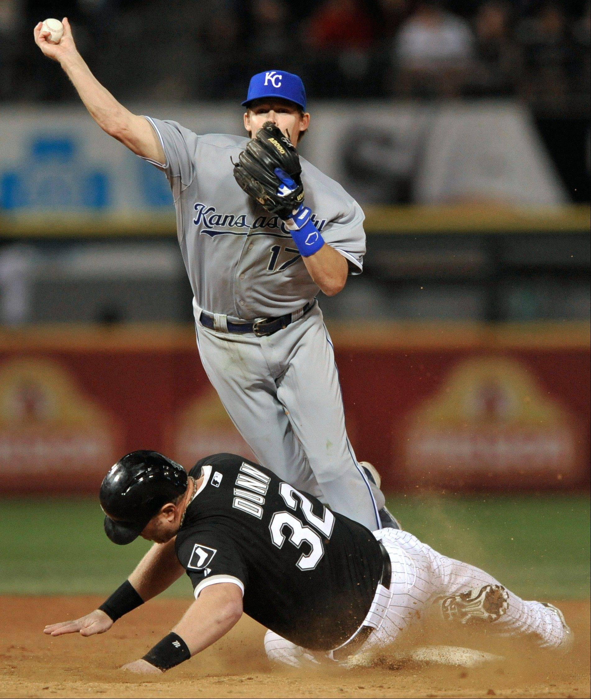 Kansas City Royals second baseman Chris Getz throws to first base after forcing out Chicago White Sox's Adam Dunn at second base during the ninth inning of a baseball game in Chicago, Saturday, July 27, 2013. Paul Konerko was safe at first. Kansas City won 1-0.