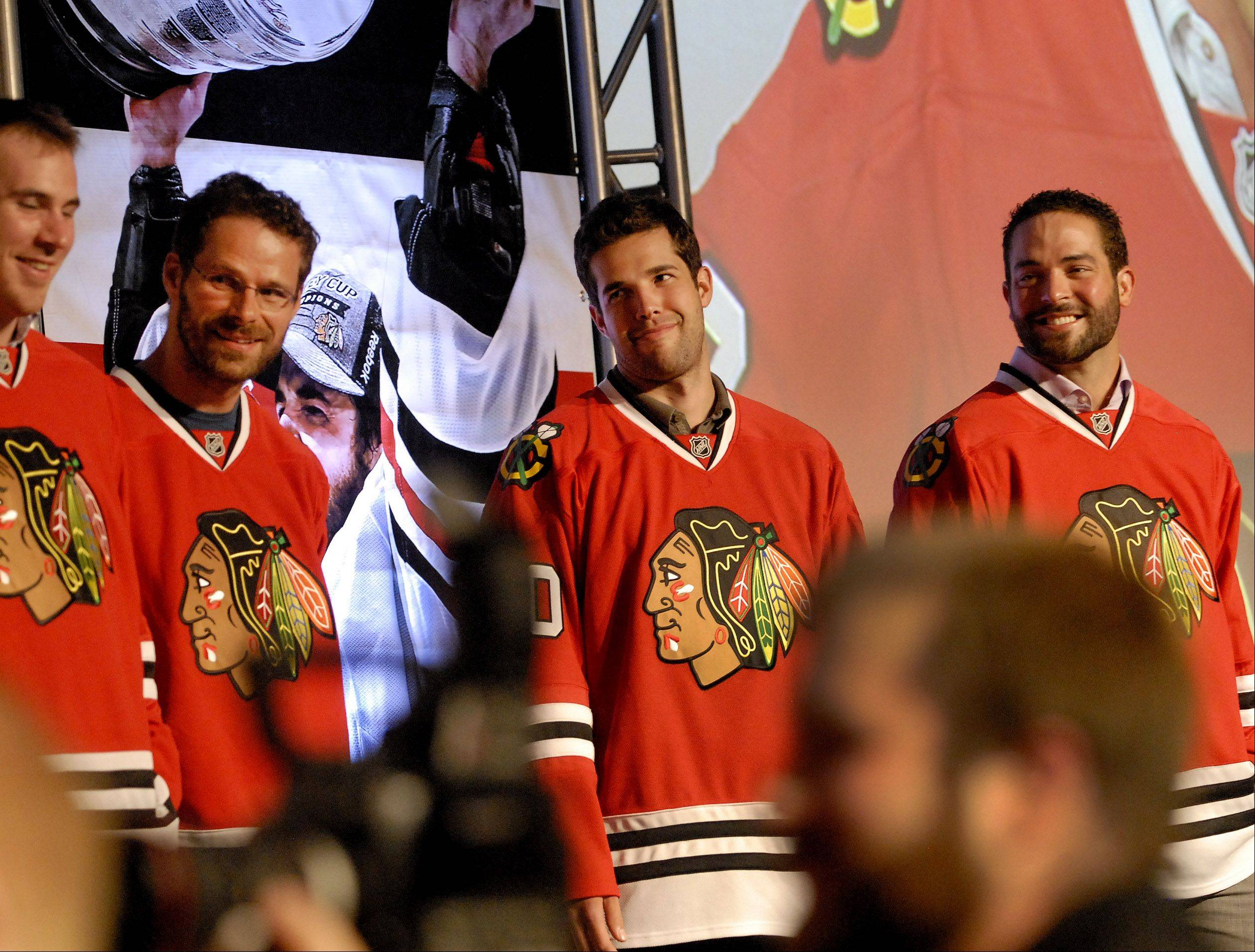 Corey Crawford, center, looks sheepish after being mentioned by Jonathan Toews during the introductions at the annual Blackhawks Convention. Crawford has been inivted to camp for Team Canada next month.