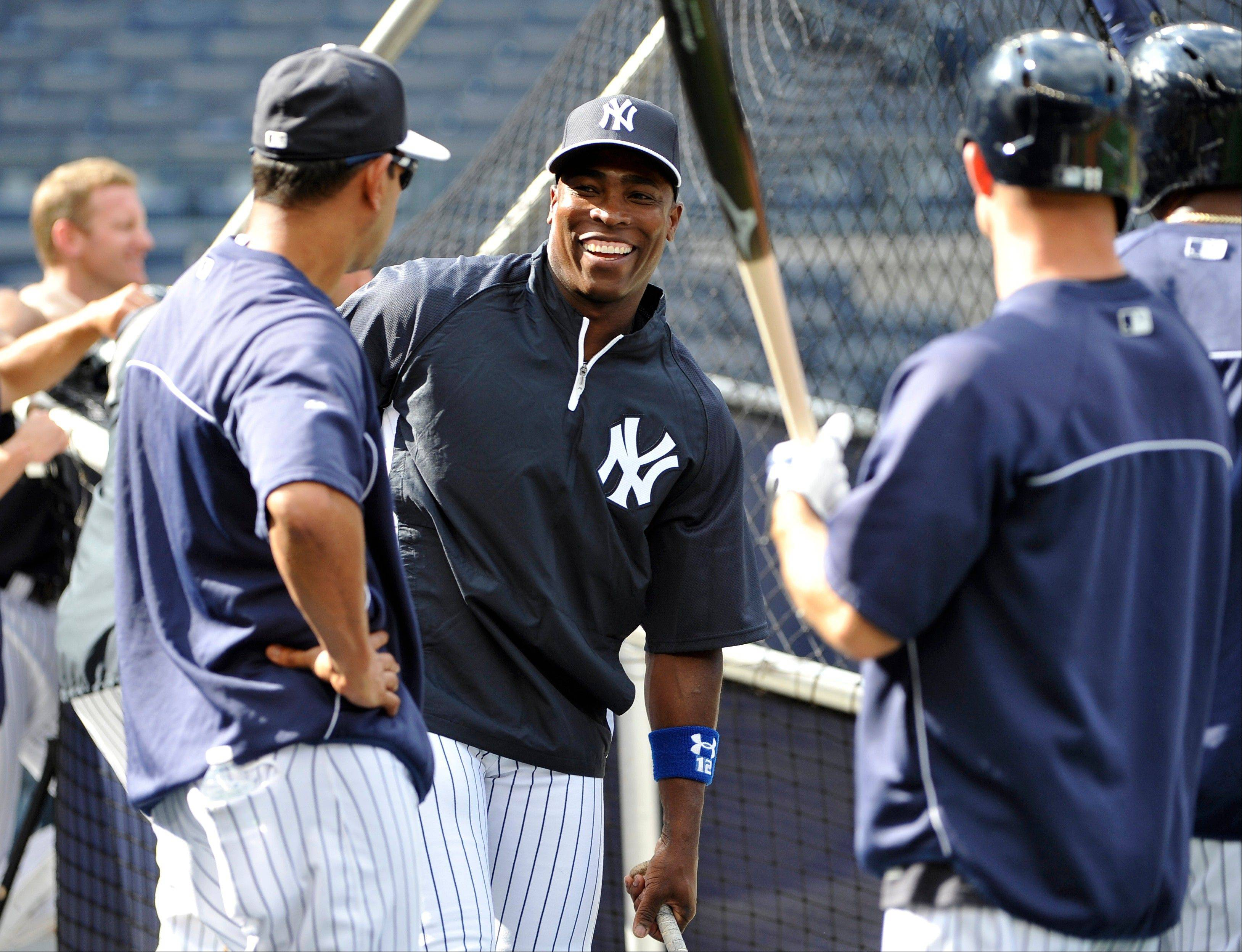 Alfonso Soriano, center, is greeted by New York Yankees teammates during batting practice before Friday's game against the Tampa Bay Rays at Yankee Stadium.