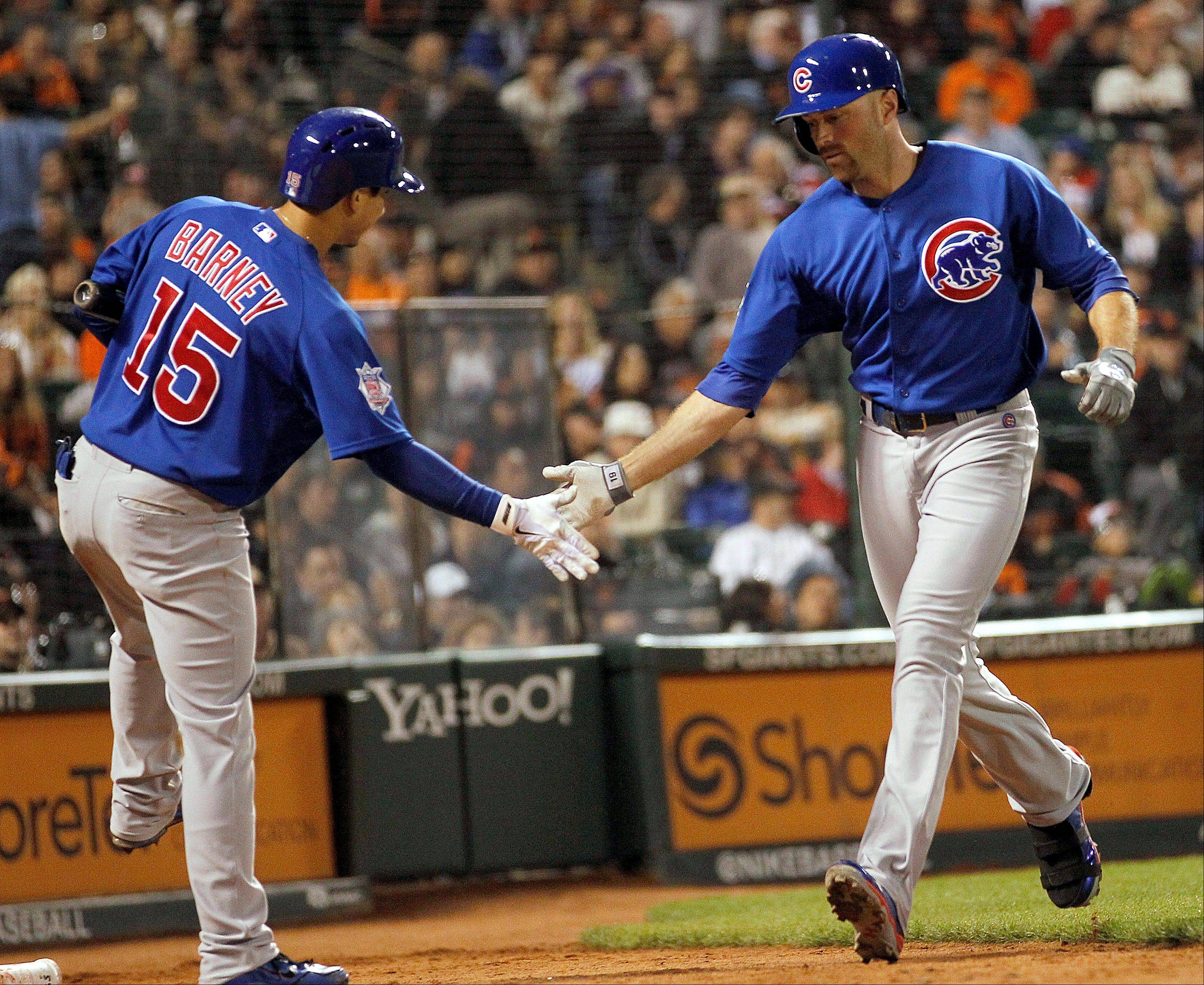 The Cubs' Nate Schierholtz, right, is congratulated by Darwin Barney after hitting a solo home run against Giants relief pitcher Sergio Romo Saturday night in San Francisco.