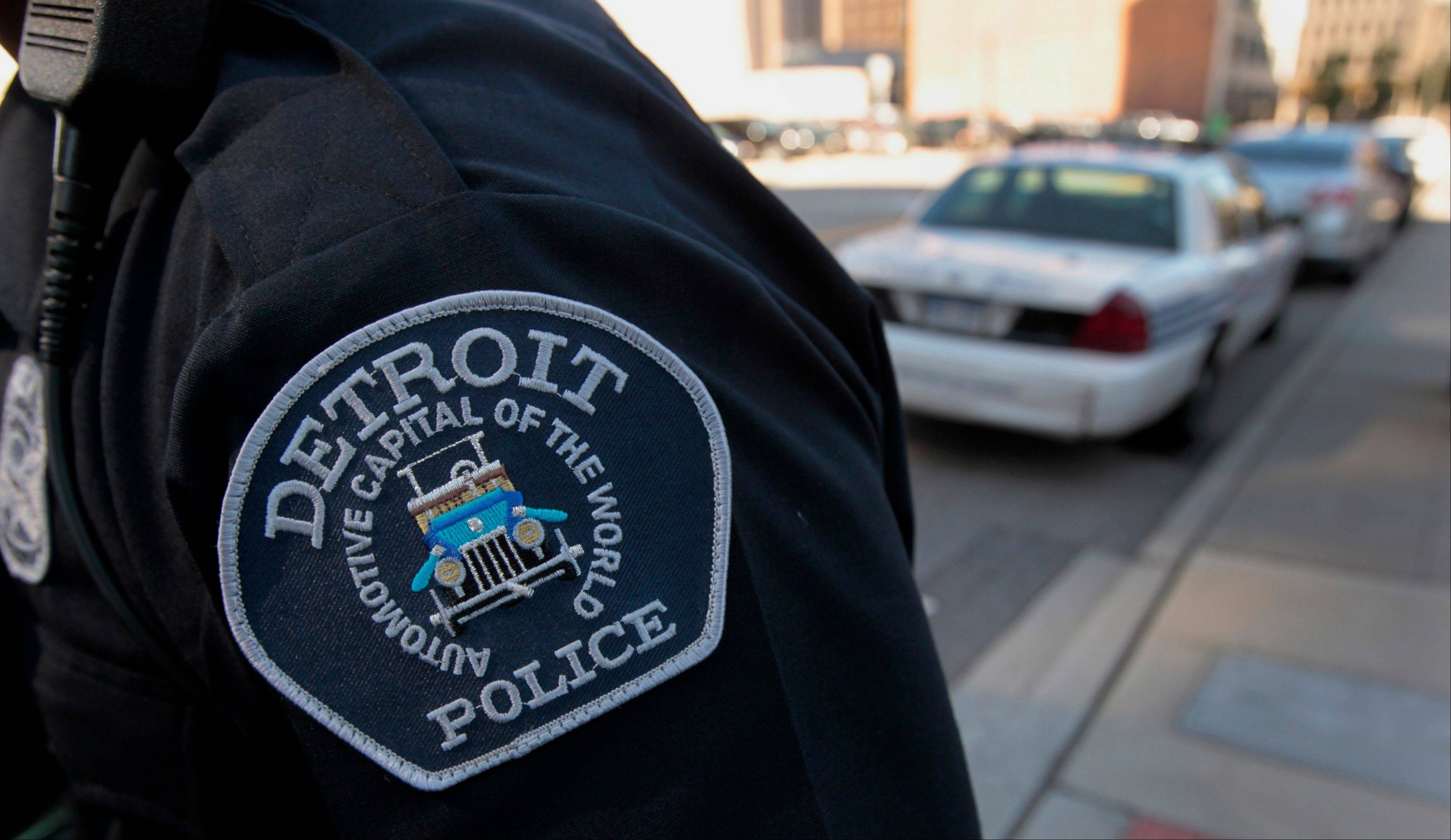 The emblem for the Detroit Police Department is seen on the sleeve of an officer Wednesday outside of the Theodore Levin U.S. Courthouse in Detroit. Detroit began its first court hearing after filing the biggest U.S. municipal bankruptcy. The city plans to seek a court order barring lawsuits against Michigan Governor Rick Snyder that are related to the case.