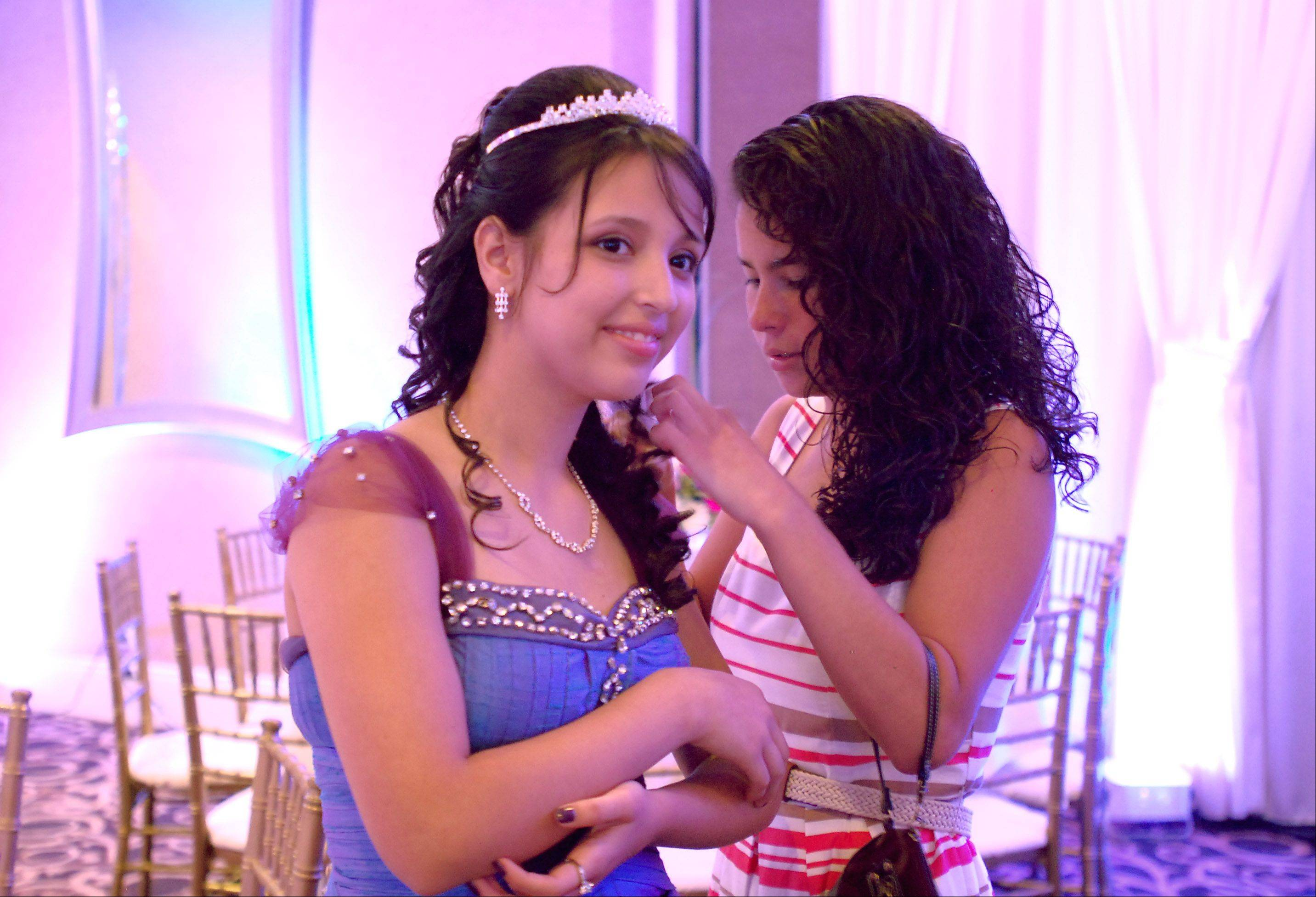 Zareli Saavedra, 14, of Hanover Park gets a little help from Eugenia Aguilera, 19, of Schaumburg. Zareli, who�s battling brain cancer, had her dream of a quincea�era came true thanks to the Make-A-Wish foundation Sunday in Streamwood.