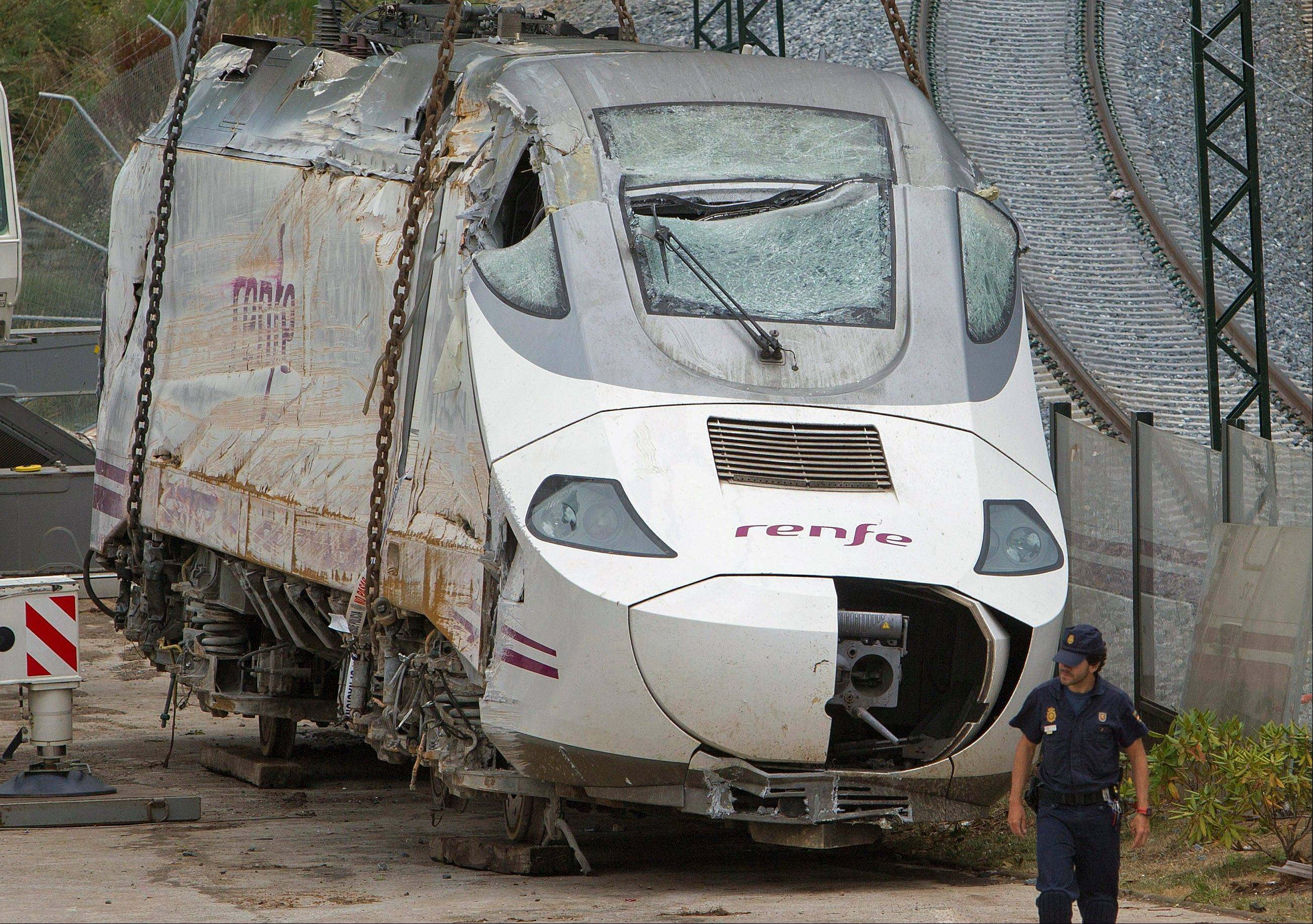 Police stand guard as wreckage of a crashed train is seen ready to be deposited in Santiago de Compostela, Spain, Sunday.