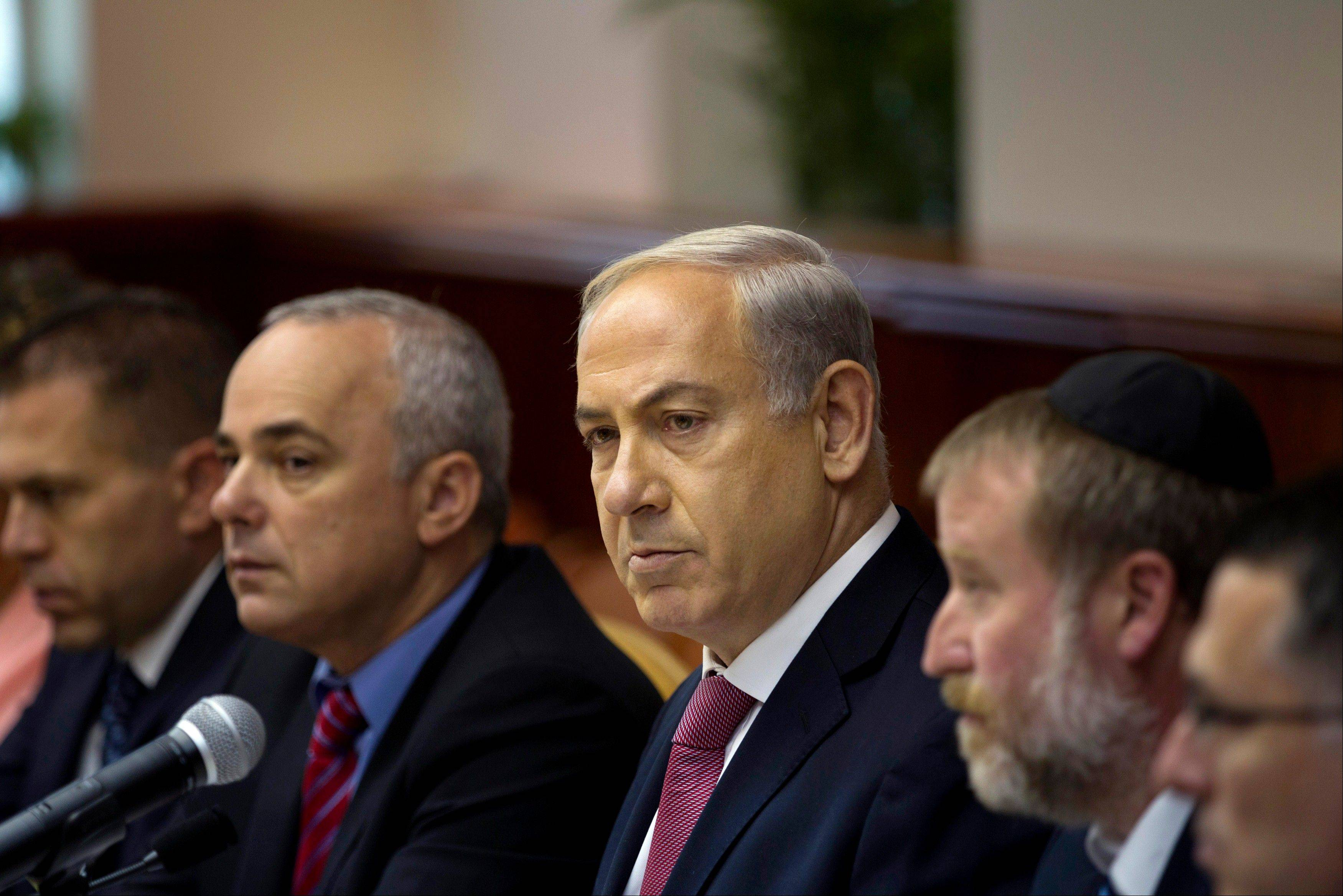 "Israel's Prime Minister Benjamin Netanyahu, center, attends the weekly cabinet meeting in Jerusalem, Sunday. Netanyahu coaxed his skeptical coalition partners Sunday to agree to free Palestinian prisoners as part of U.S efforts to resume peace talks, calling the deal a ""tough decision"" that he took for the good of the country."