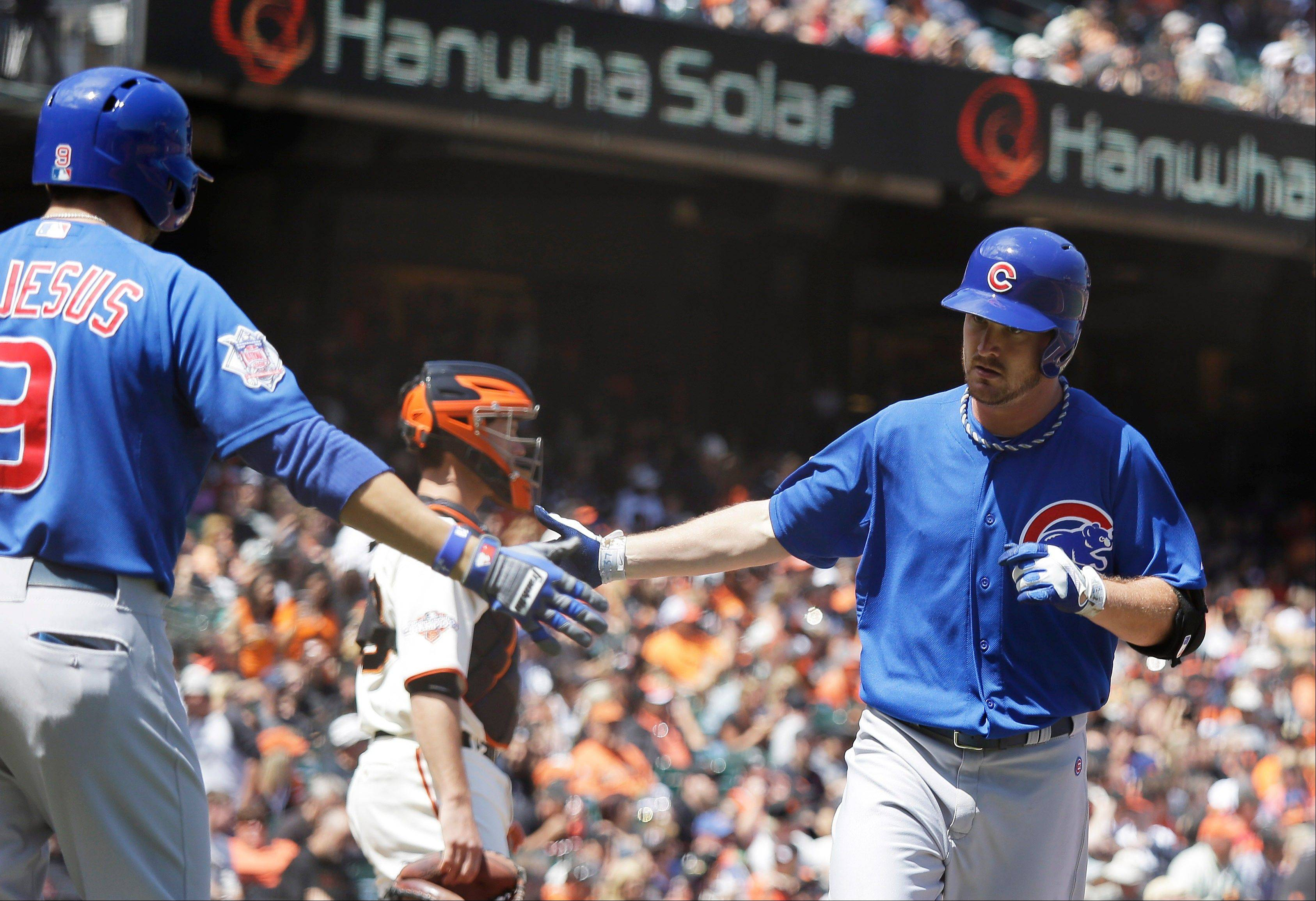 Cubs pitcher Travis Wood, right, is greeted by teammate David DeJesus, left, after hitting a home run off San Francisco Giants starting pitcher Tim Lincecum during Sunday�s fifth inning.