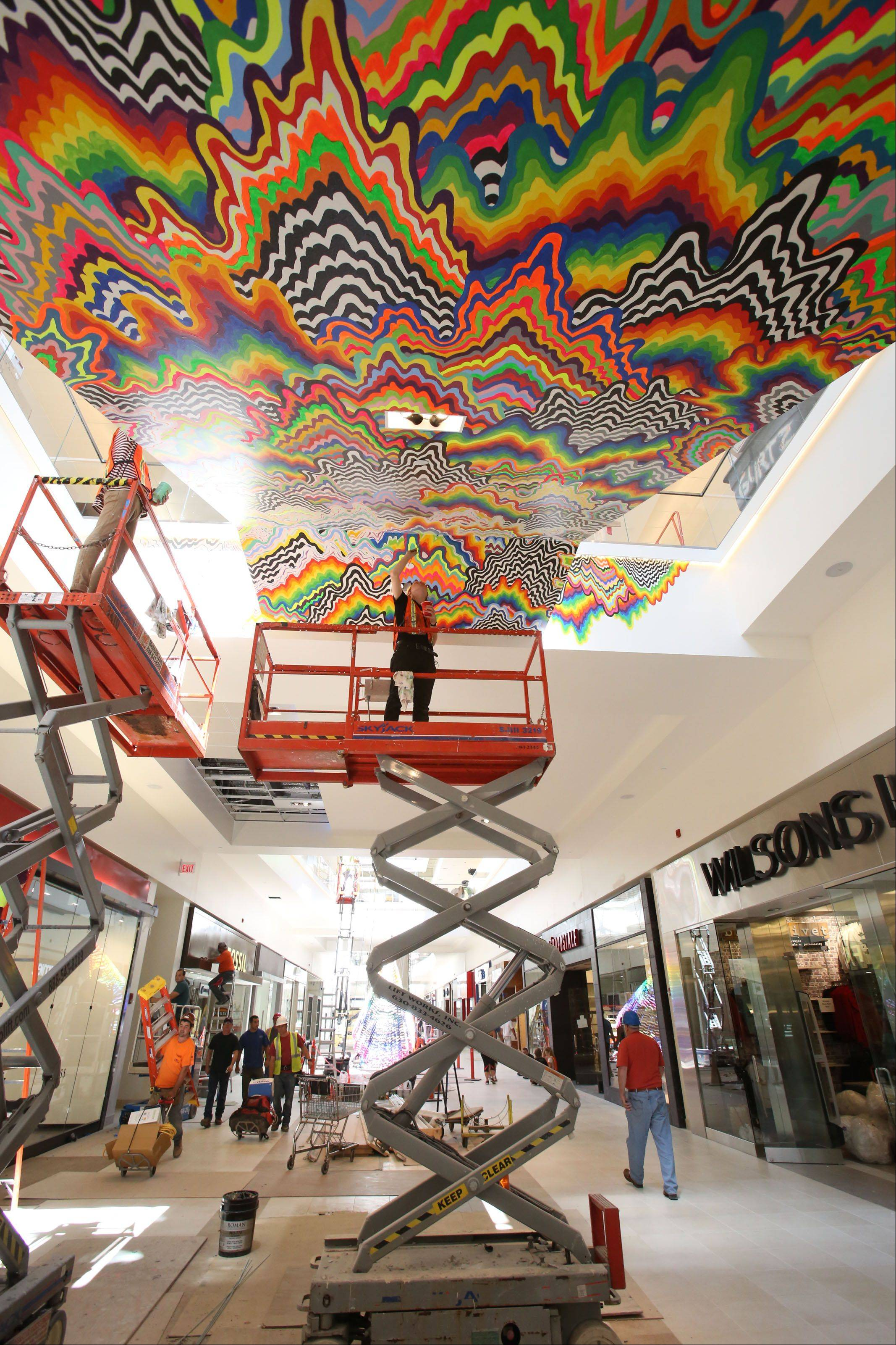 Workers attach an art piece by Jen Stark to the ceiling of the Fashion Outlets of Chicago in Rosemont in preparation for the mall's opening Thursday.