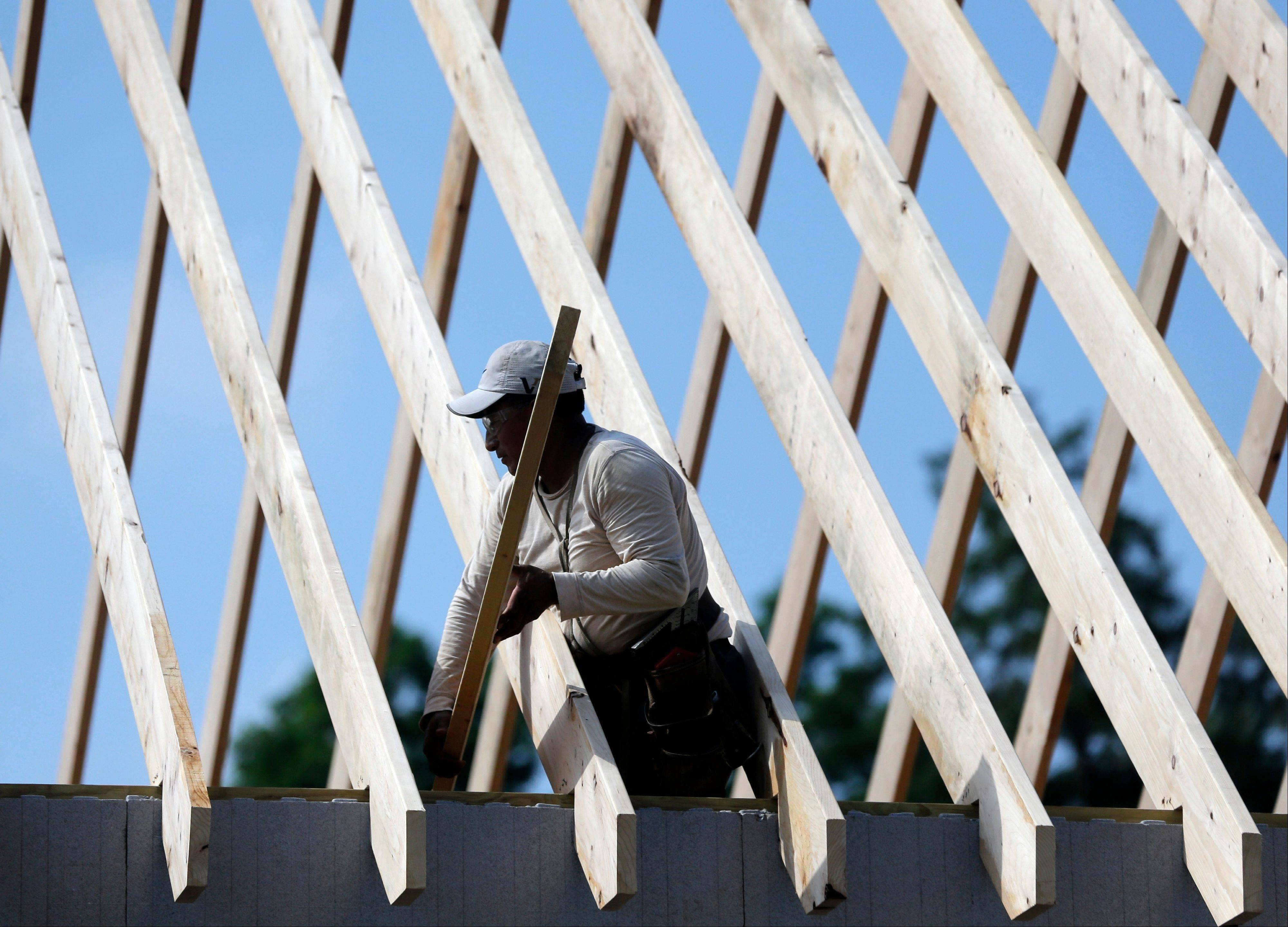 A worker works on the roof of a zero net energy home at The Preserve at Mountain Vista in New Paltz, N.Y.