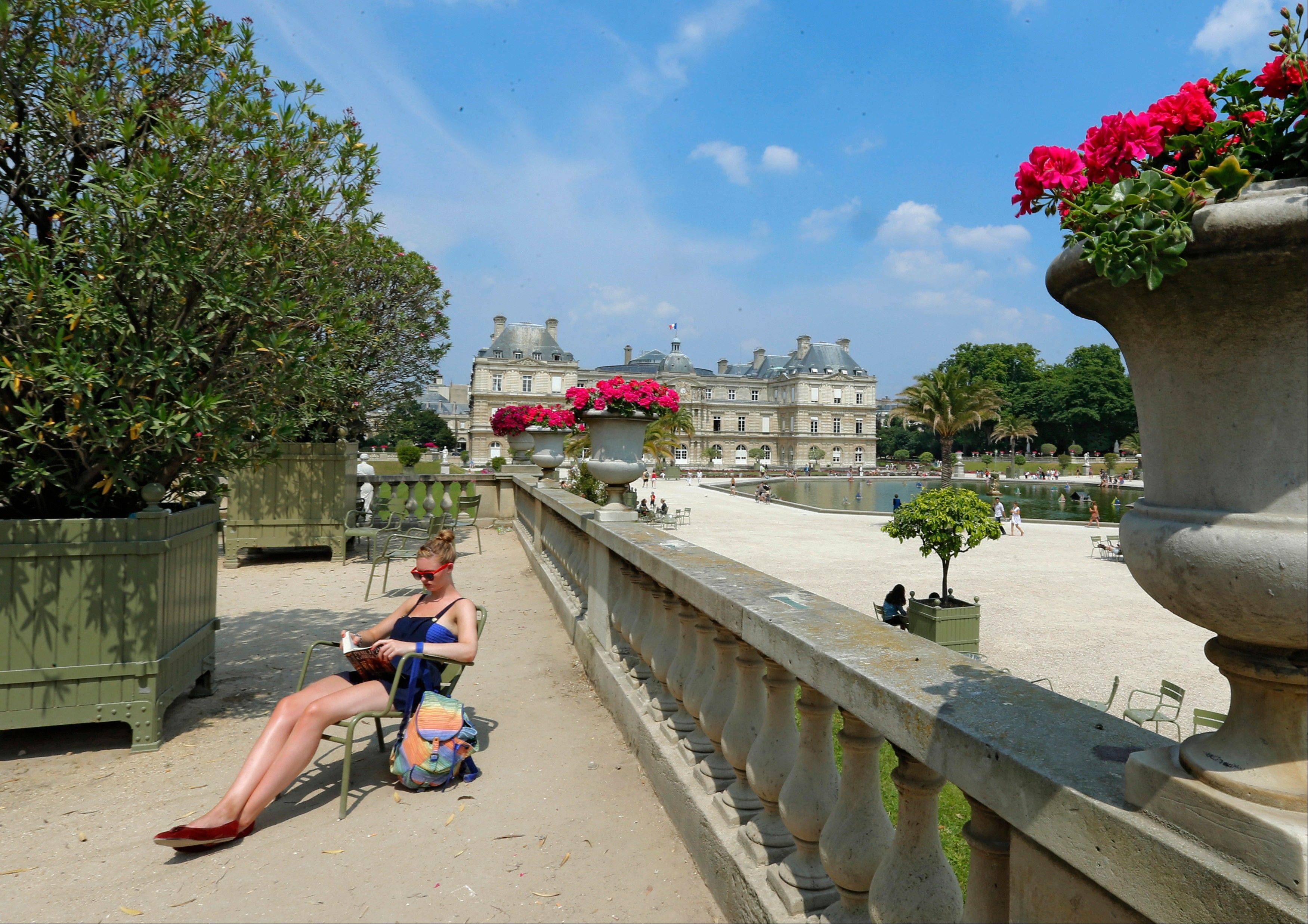 A women sunbathes in the Luxembourg gardens in Paris.