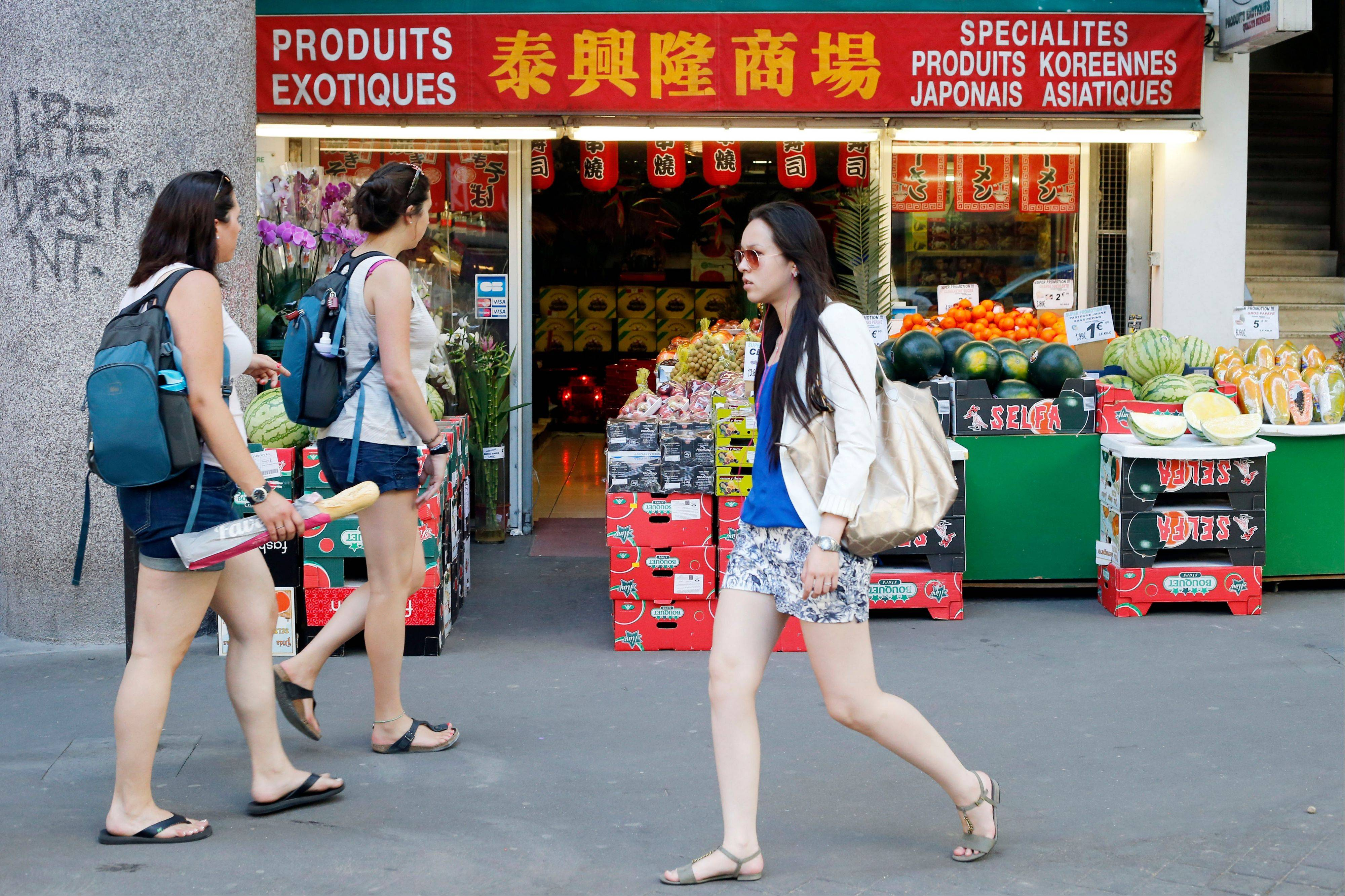 Tourists at left, walk front of a shop at the Chinese quarter in the 13th district of Paris, the largest Chinatown in Europe.