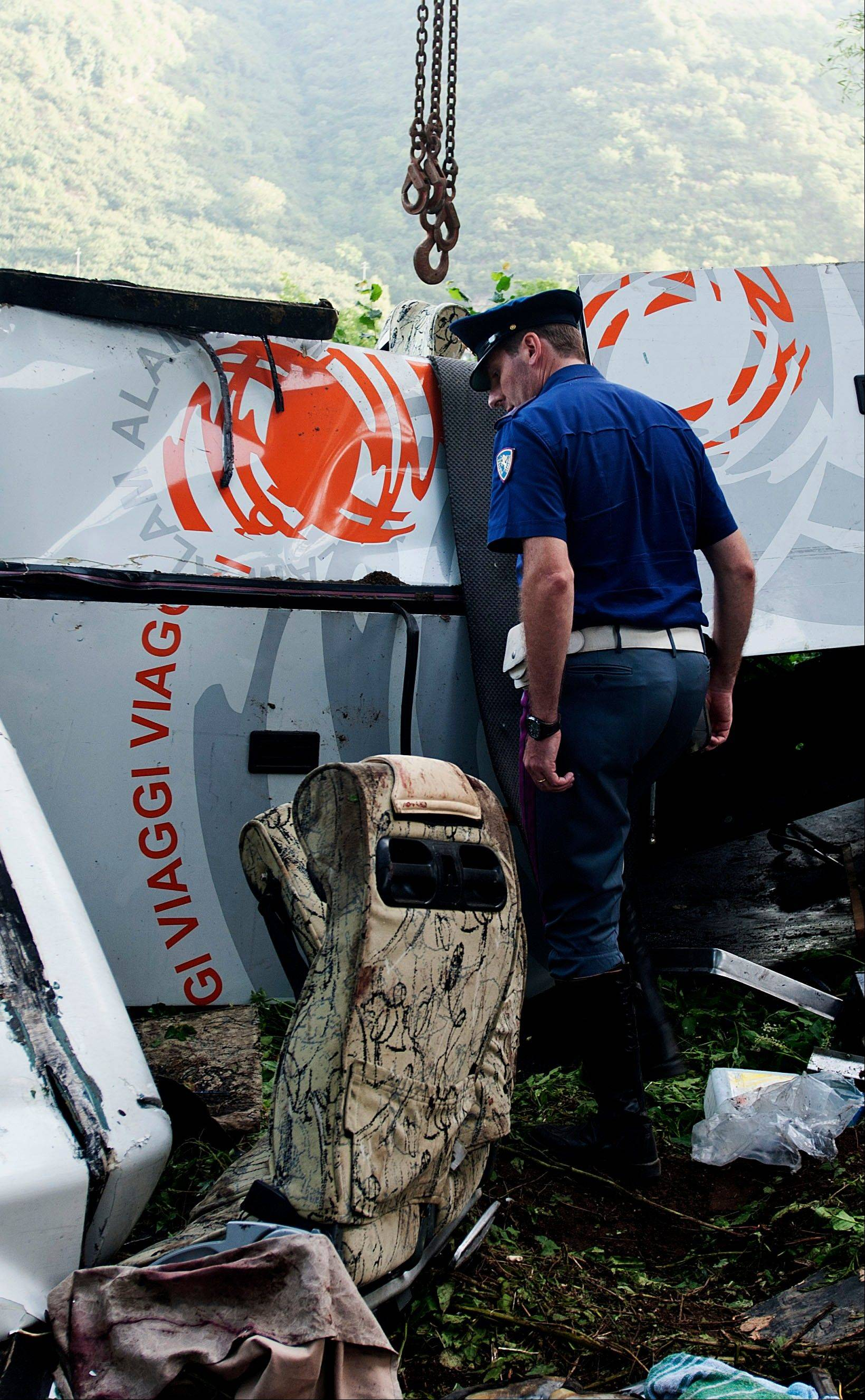 A police officer looks at in the wreckage of a bus which crashed off a highway near Avellino, southern Italy, Monday, July 29, 2013. Rescuers wielding electric saws cut through the twisted wreckage of an Italian tour bus for survivors of a crash in southern Italy that killed at least 37 people after it crashed into traffic and plunged into a ravine on Sunday night. Reports said as many as 49 people, mostly Italians, had been aboard the bus when it ripped through a guardrail, then plunged some 30 meters (100 feet) off a viaduct near a wooded area.