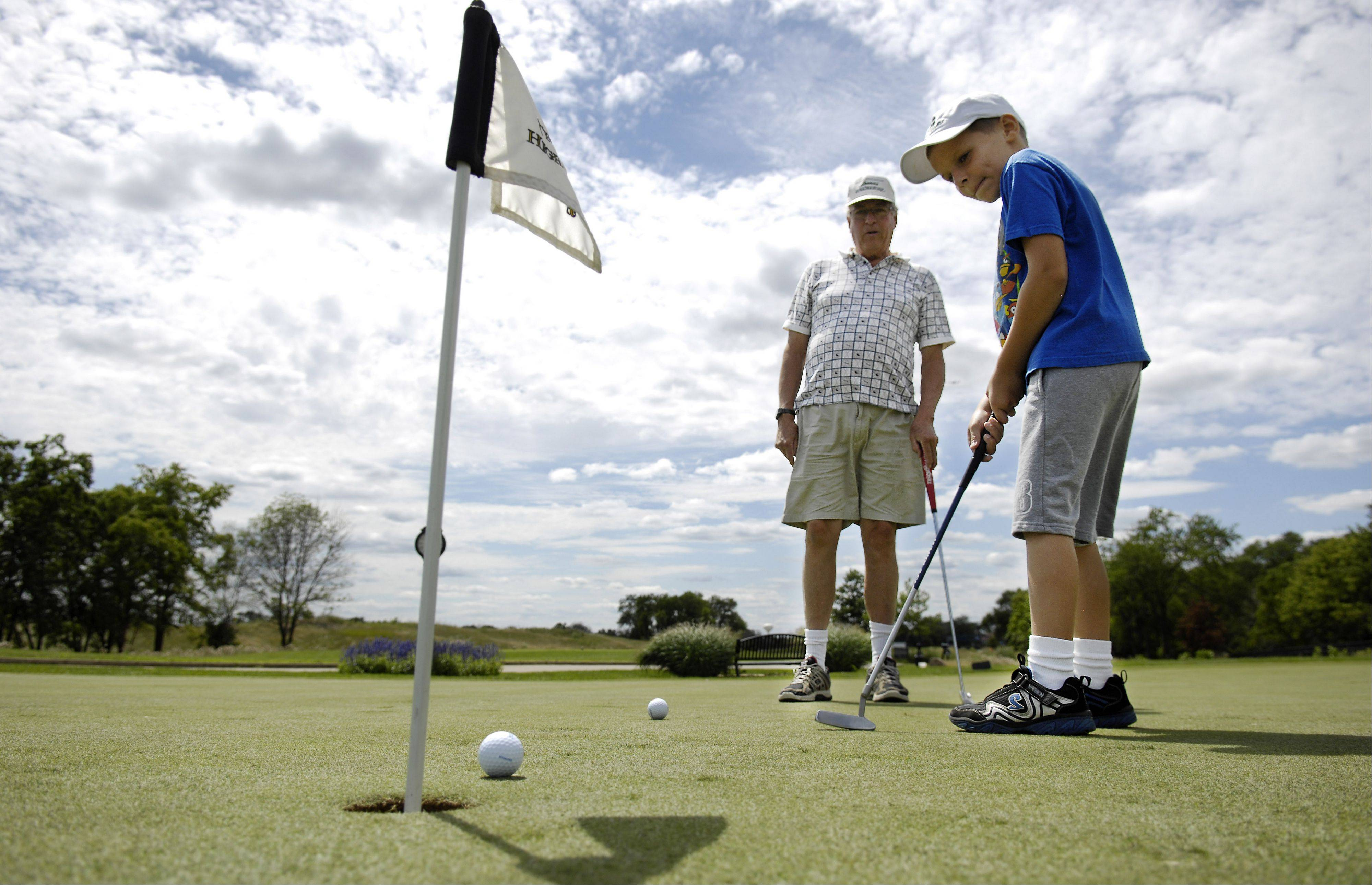 Scott Wagner of Elgin works with his grandson A.J. Csornok, 7, on his short game at The Highlands of Elgin Wednesday. A.J. is visiting from Rapid City, SD. A.J. has been learning to golf for a couple of years. They hit a bucket of balls on the driving range before moving on to the practice green.