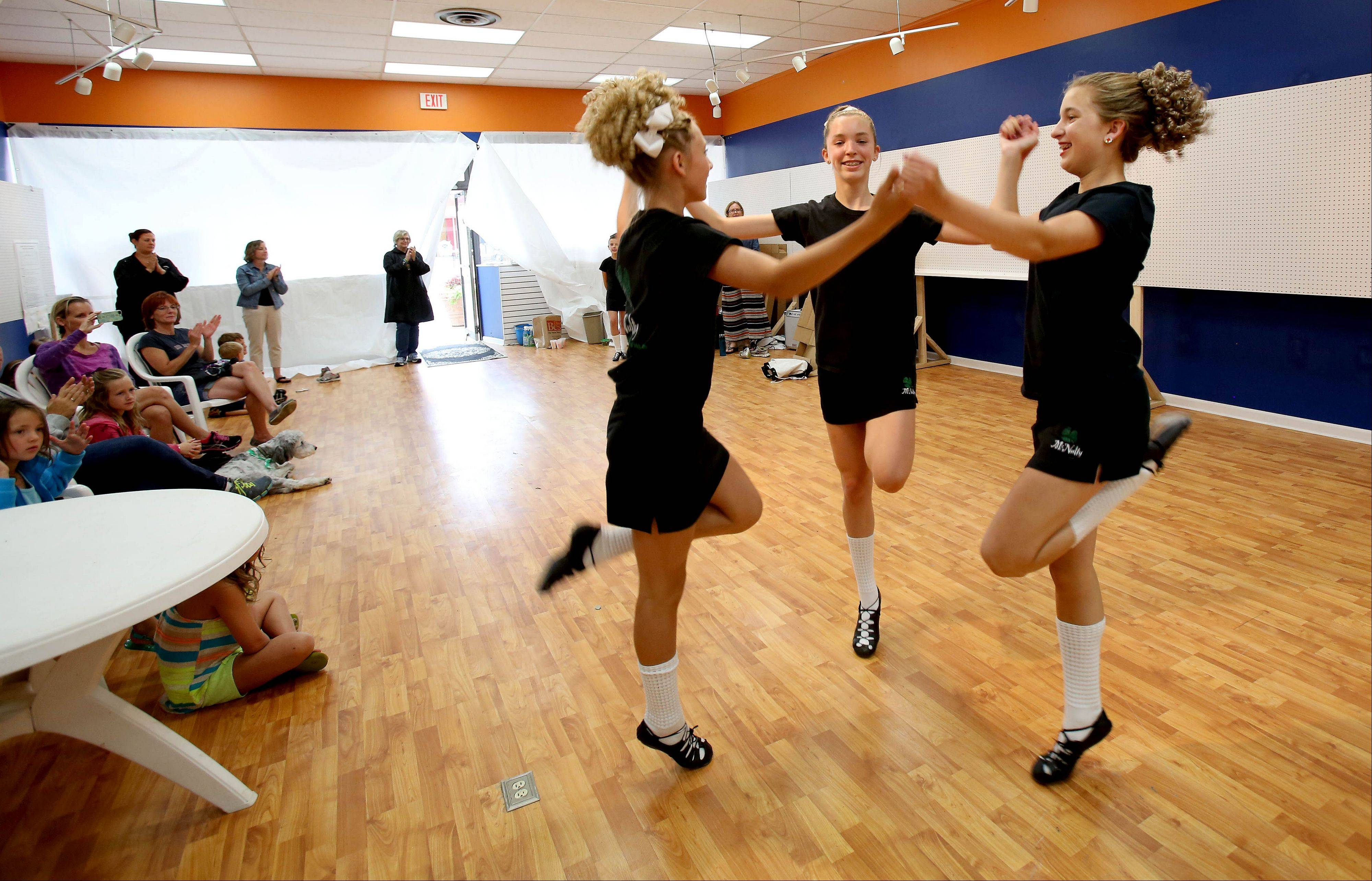 Left to right, Julia Robleski, 13, of Wheaton, Dana Scholtens, 16, of Wheaton, and Kendall McPartlin, 12, of Glen Ellyn, with the McNulty Irish Dancers, perform in an empty store along Main Street on Friday as part of the Glen Ellyn Sidewalk Sale. The group performs every year, but usually in the street. Rain forced many stalls to close up early and forced the dancers indoors.