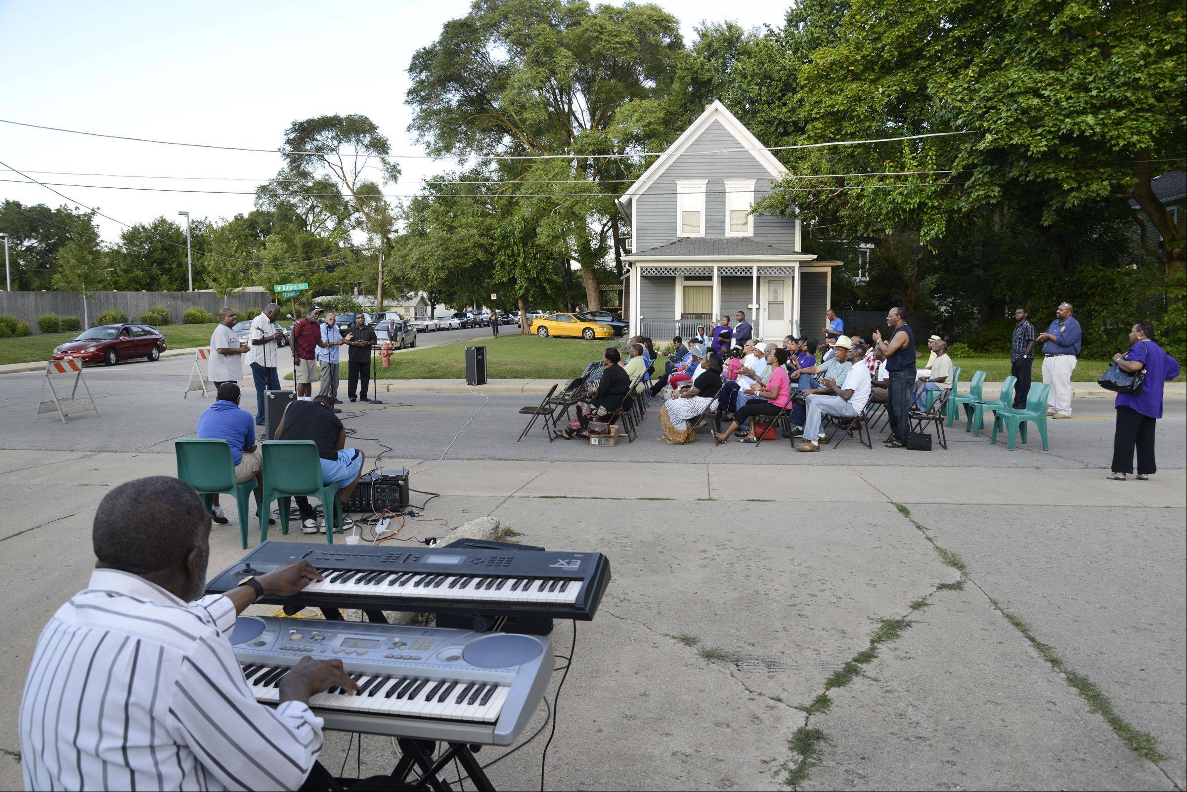 Gifford Street south of Fremont Street is closed as the St. James AME male chorus sings in the street as the African American Christian Ministers Alliance hosted their annual citywide Street Revival Tuesday in Elgin.